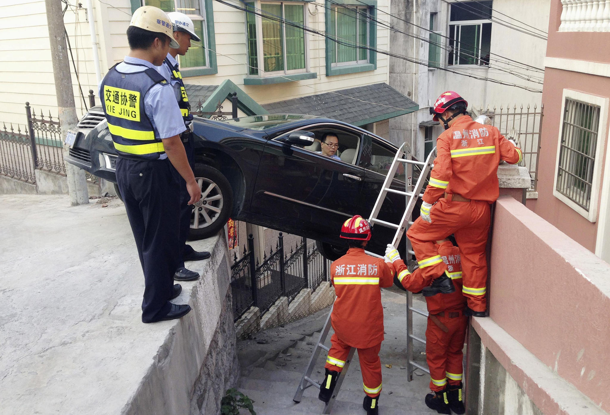 Rescue workers try to help a driver out of his car, after the vehicle was stuck over an alley in Wenzhou, Zhejiang province