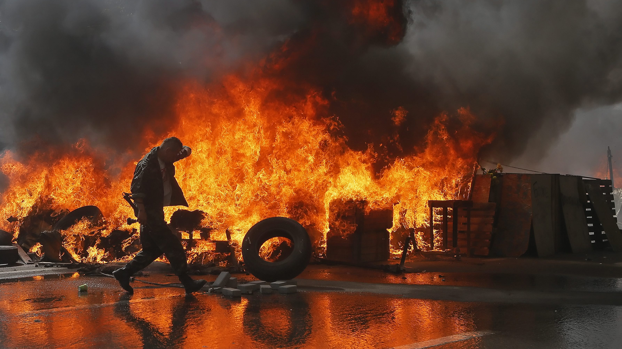 A Maidan activist burns tires during a protest against Ukrainian authorities trying to clean the main Kiev's street of Khreschatyk near the Independence square in downtown Kiev, Ukraine, 07 August 2014. Maidan activists declared they will not allow to hold a military parade in downtown Kiev during celebration of the Ukrainian Independence Day on 24 August 2014.  EPA/SERGEY DOLZHENKO
