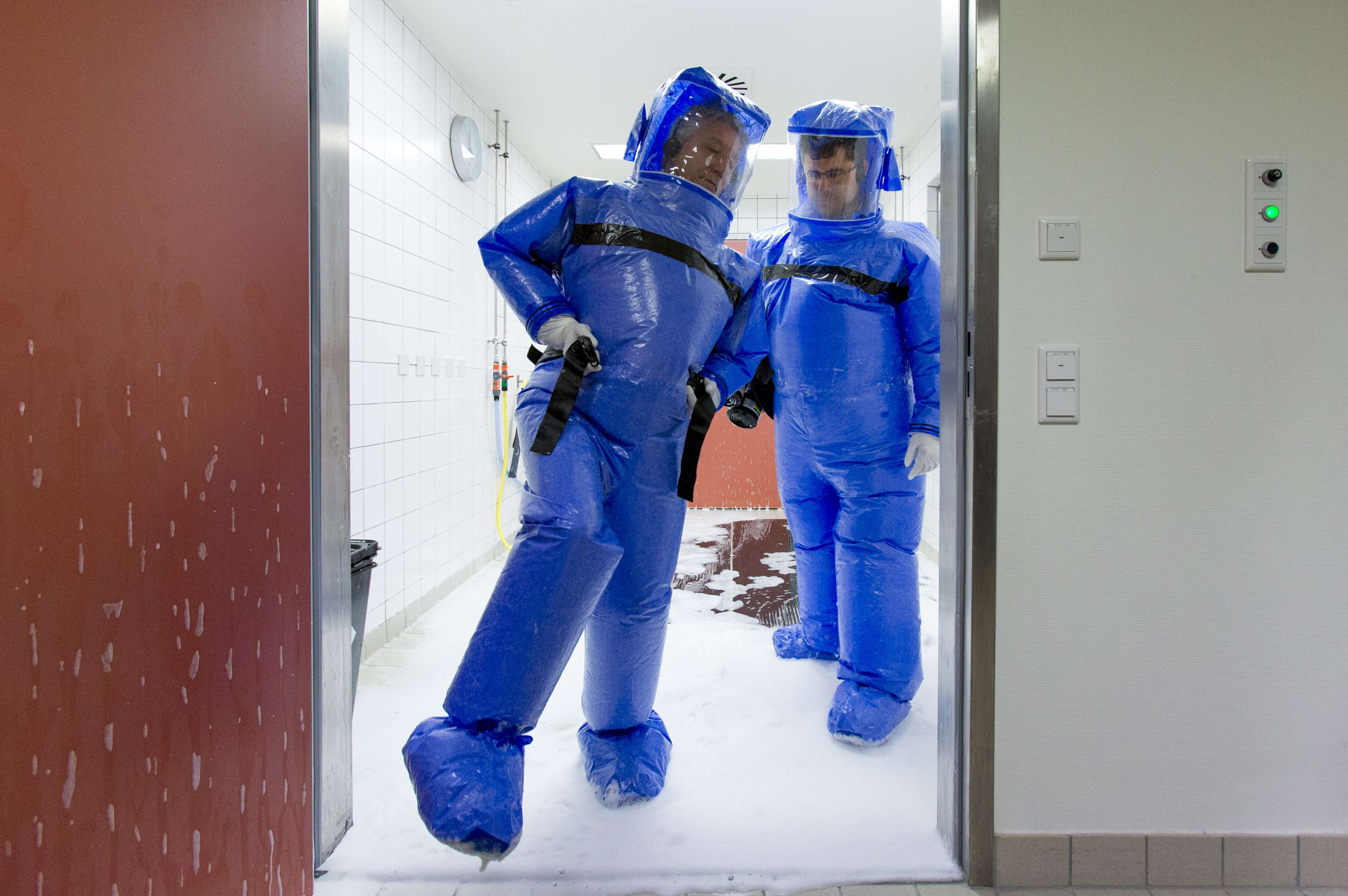 Physicians step out of disinfection chamber after cleaning their protective suits at quarantine station for patients with infectious diseases in Berlin