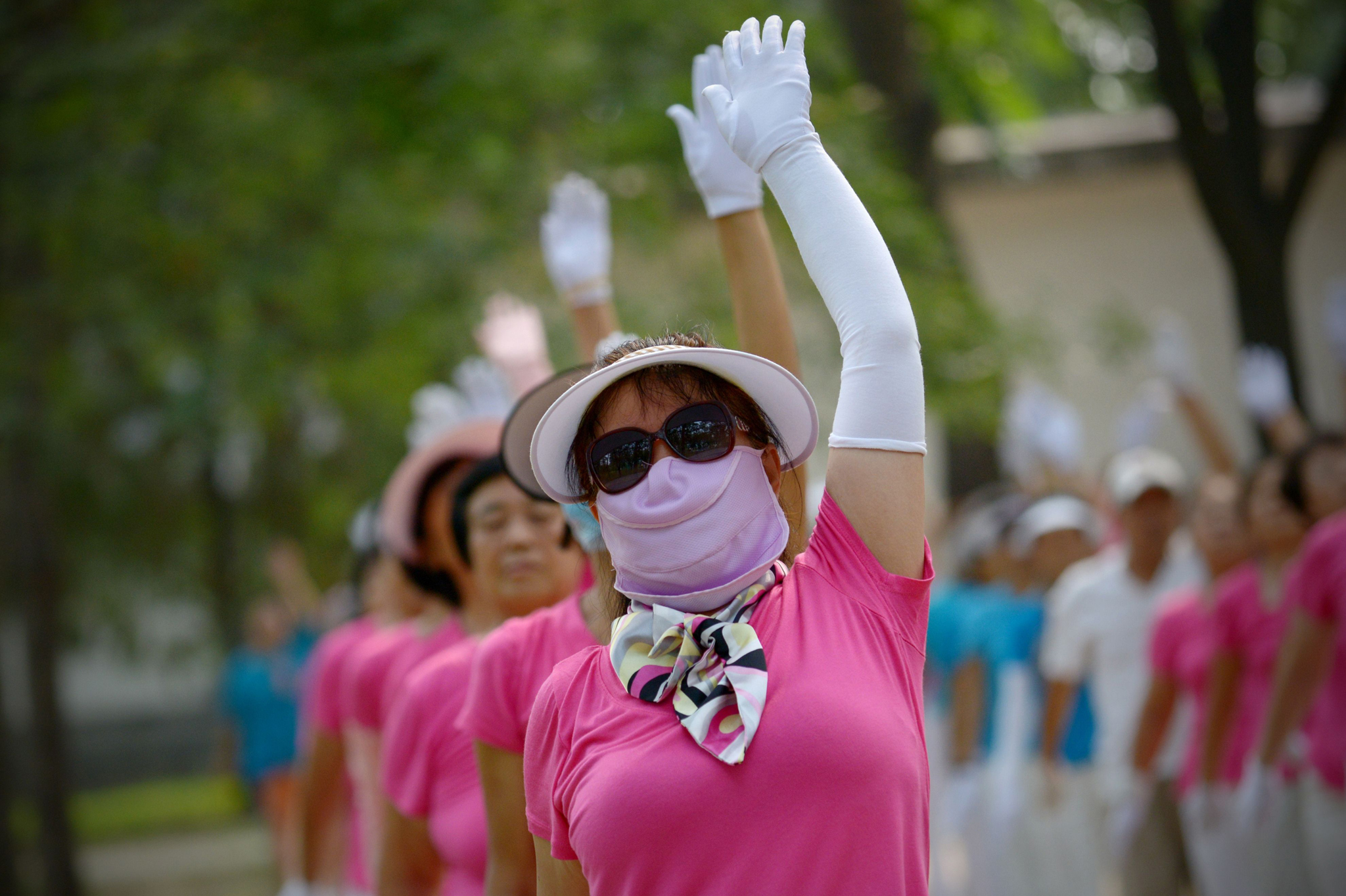 "A woman wearing a face mask exercises with others at a park in Beijing, China. Just over half of people between the ages of 20 and 39 do not exercise regularly, making them the country's ""least active"" adults."