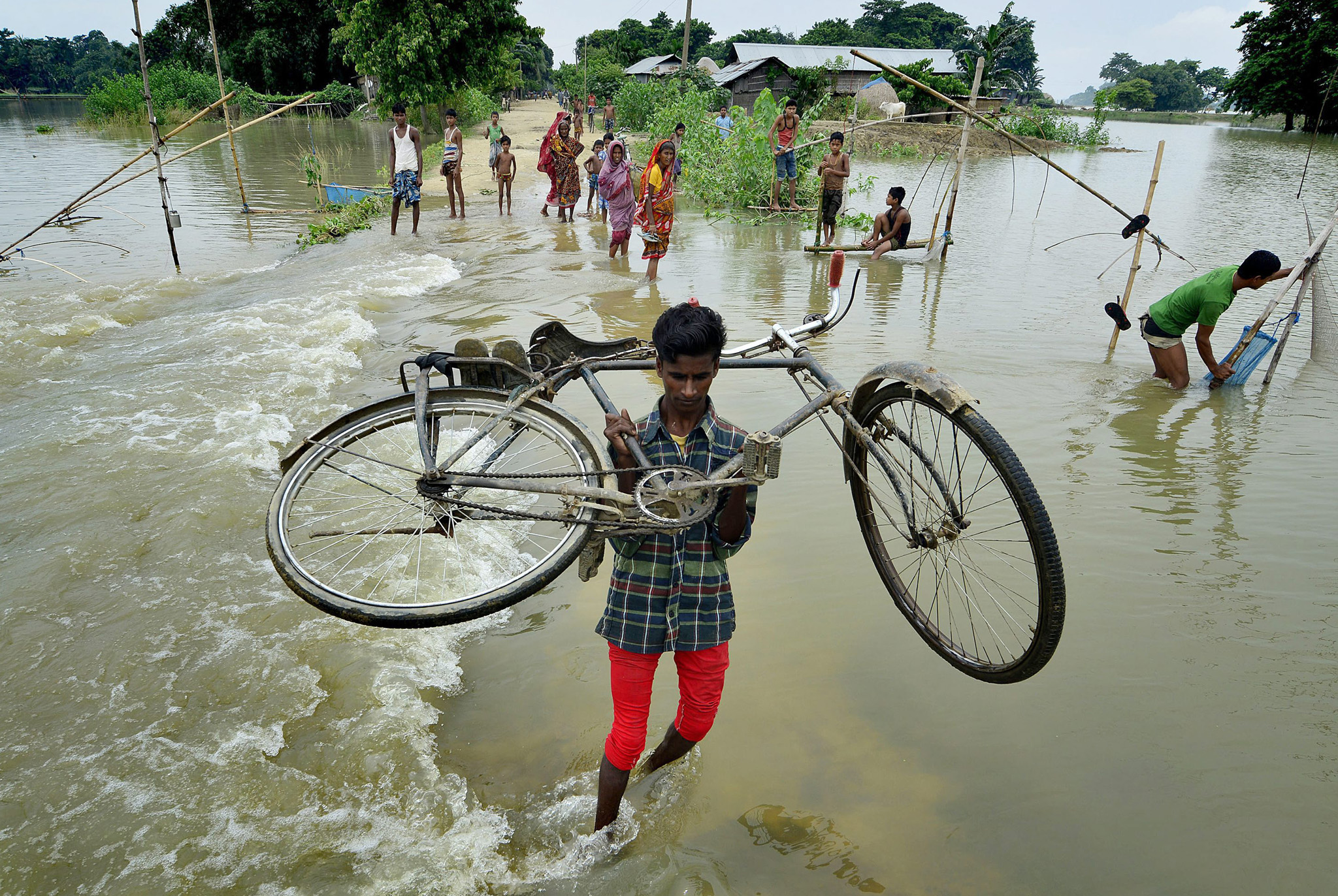 A boy carries his bicycle through floodwater in the Morigaon district of Assam state, India. Dozens of people were killed and more than a million affected as floods driven by torrential monsoon rains ravaged India's northern and eastern states.