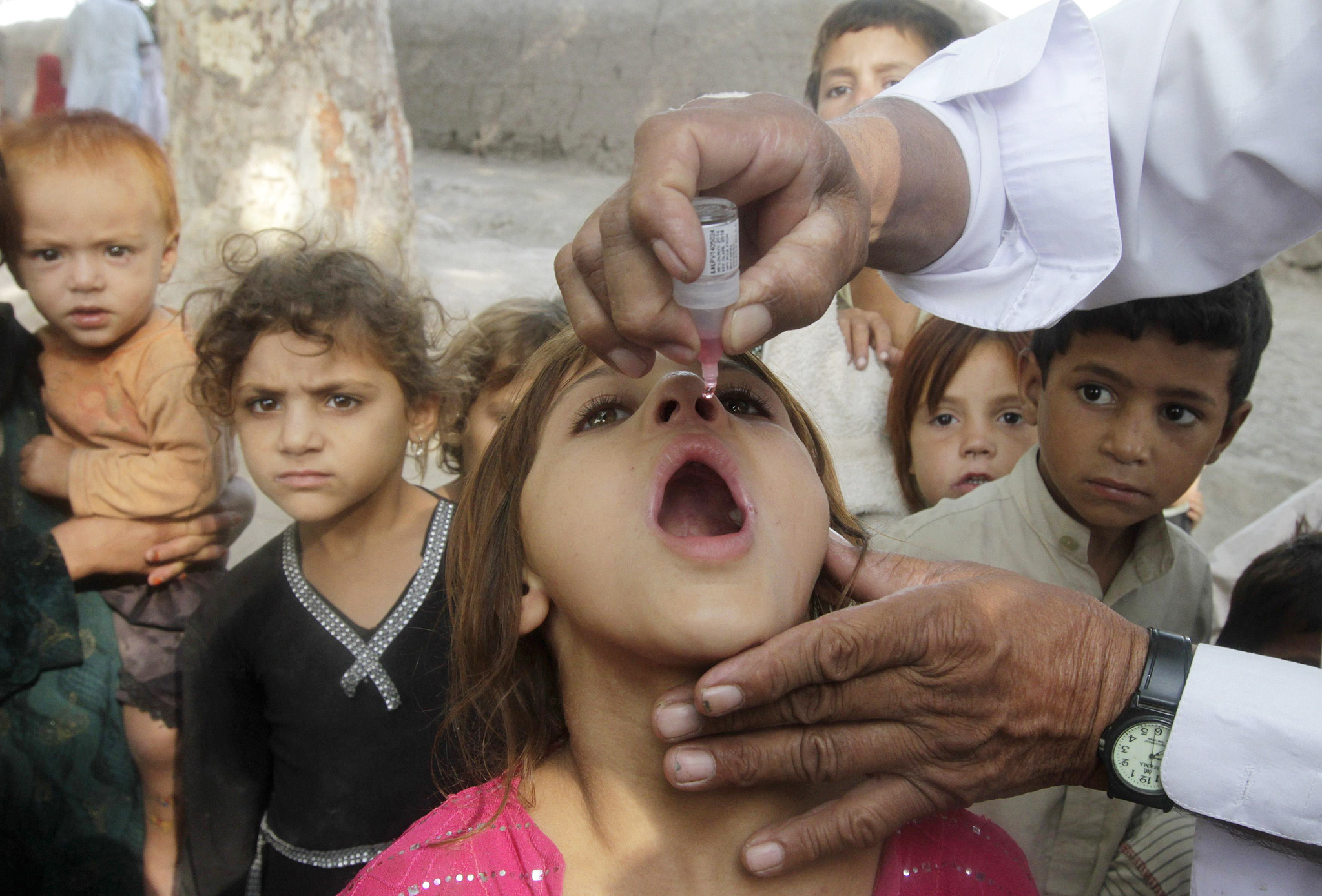 A girl receives polio vaccination during an anti-polio campaign on the outskirts of Jalalabad