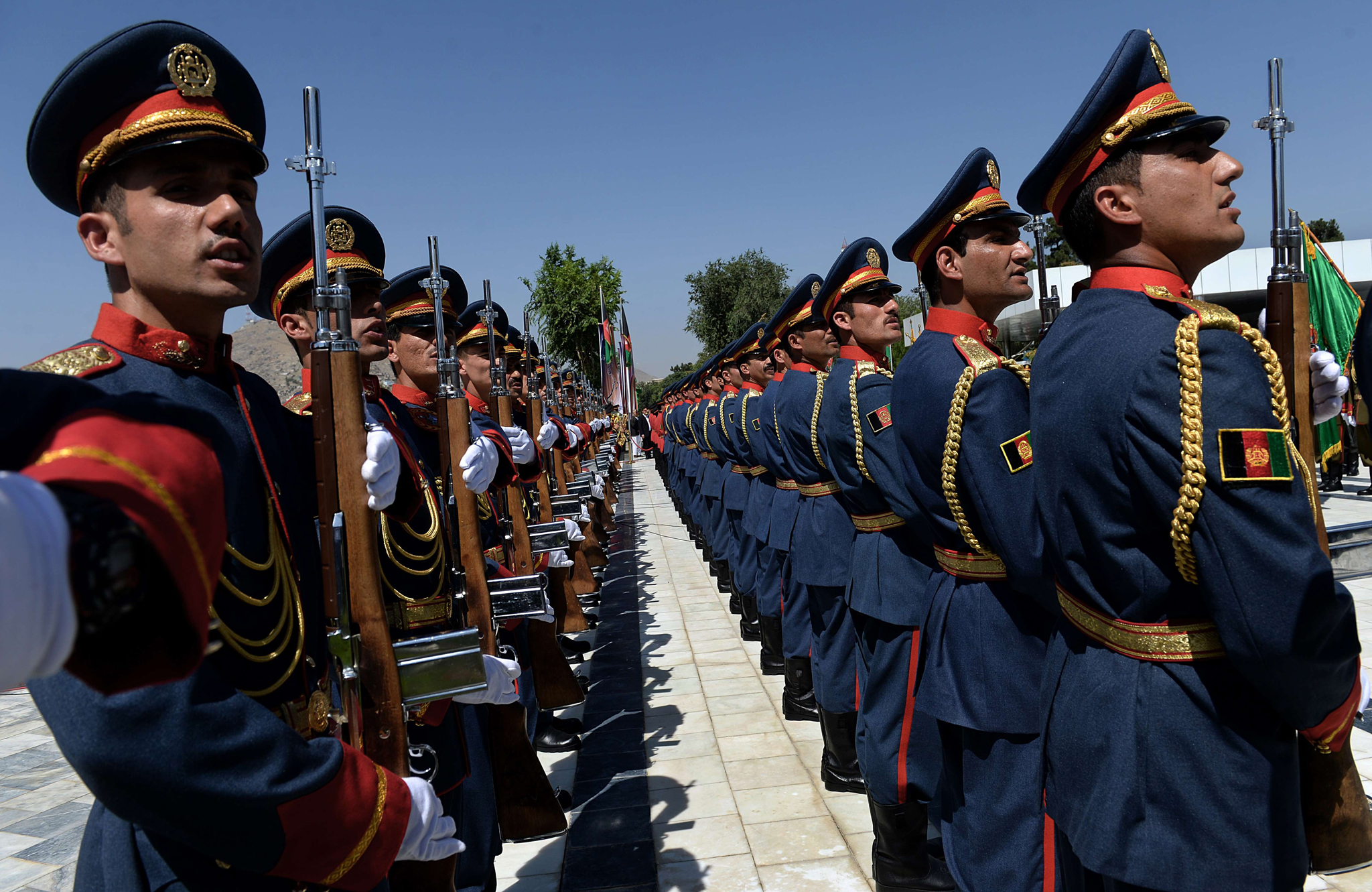 An Afghan guard of honour stands as the national anthem plays during an event to mark Independence Day at the Ministry of Defence compound in Kabul