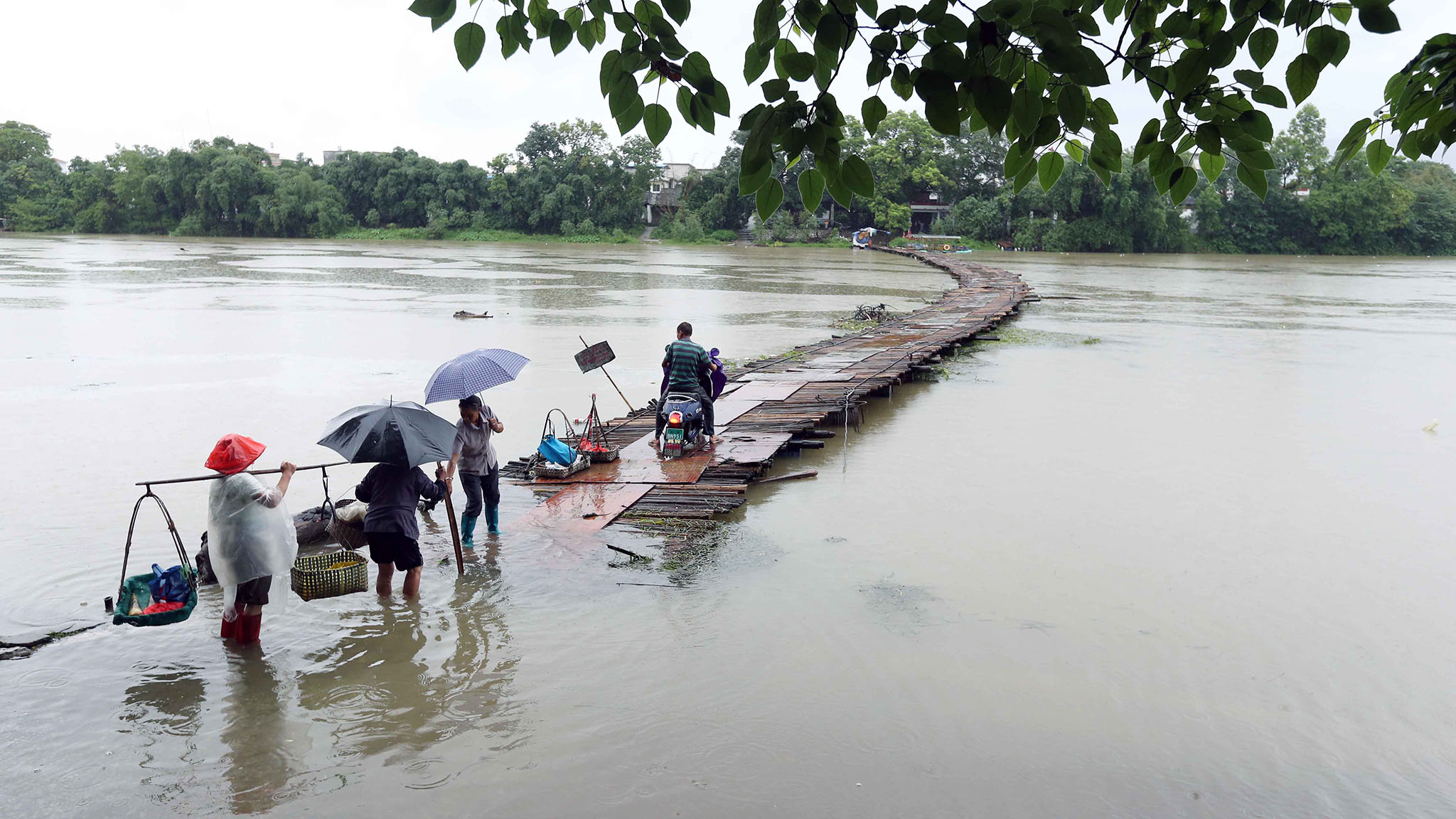 People walk along a wooden bridge submerged by floodwater in Guilin