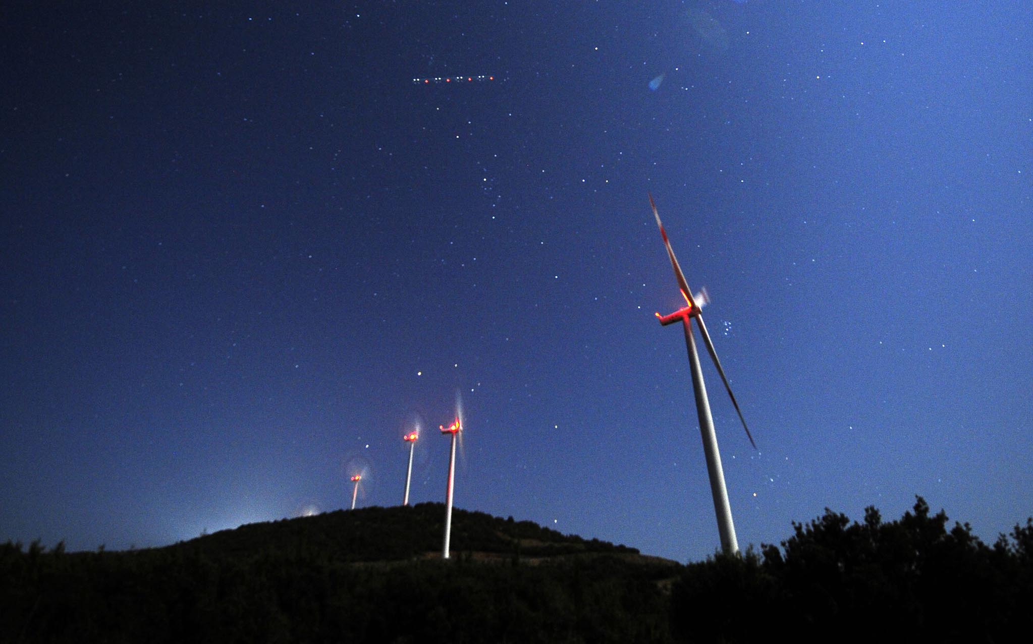 A aeroplane pases over the sky during the time of the Perseid meteor shower at a windmill farm near Bogdanci