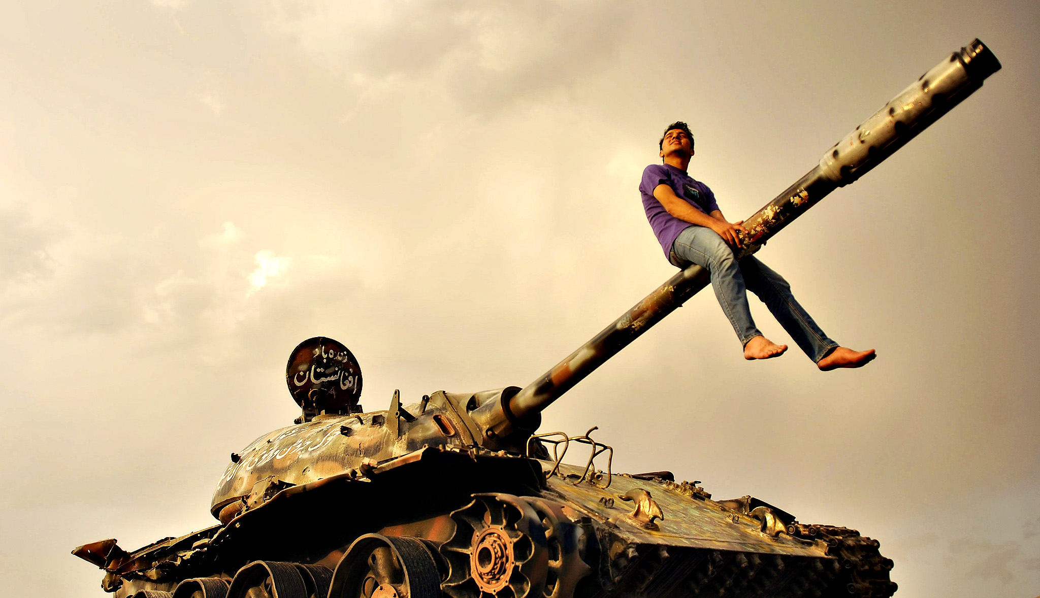 An Afghan youth sits astride the gun barrel of a Soviet-era tank, in Kabul, Afghanistan, 29 August 2014. Soviet troops occupied the country for ten years from 1979 to 1989.