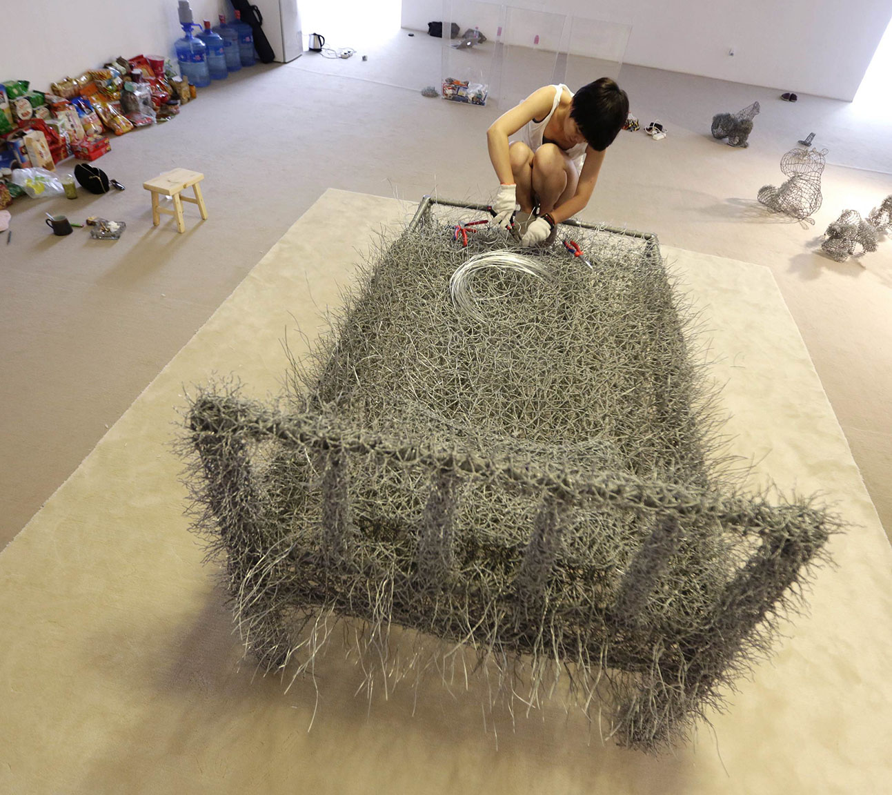 Chinese artist Zhou Jie works on an iron wire bed