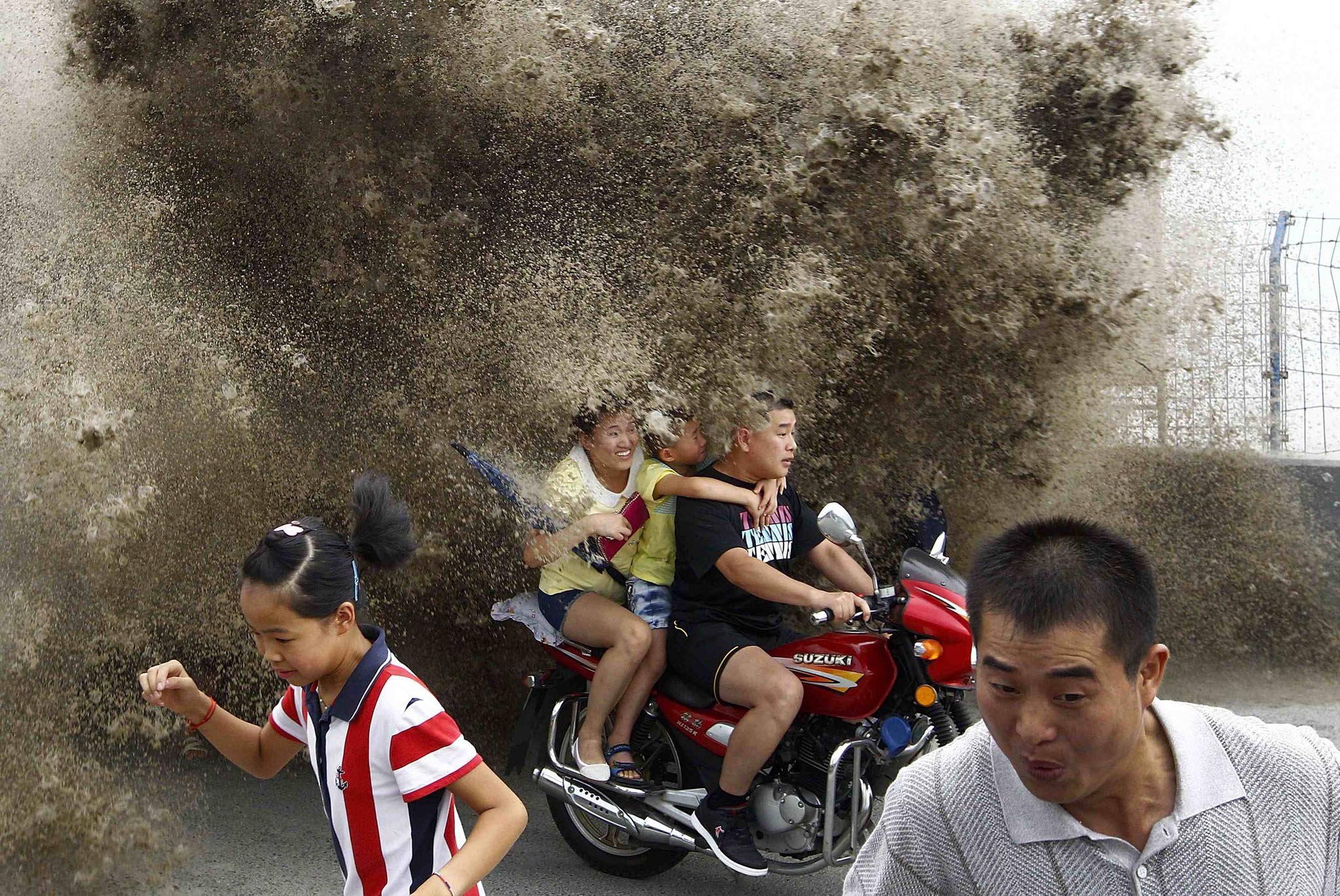 Visitors run away as waves caused by a tidal bore surge past a barrier on the banks of Qiantang River, in Hangzhou