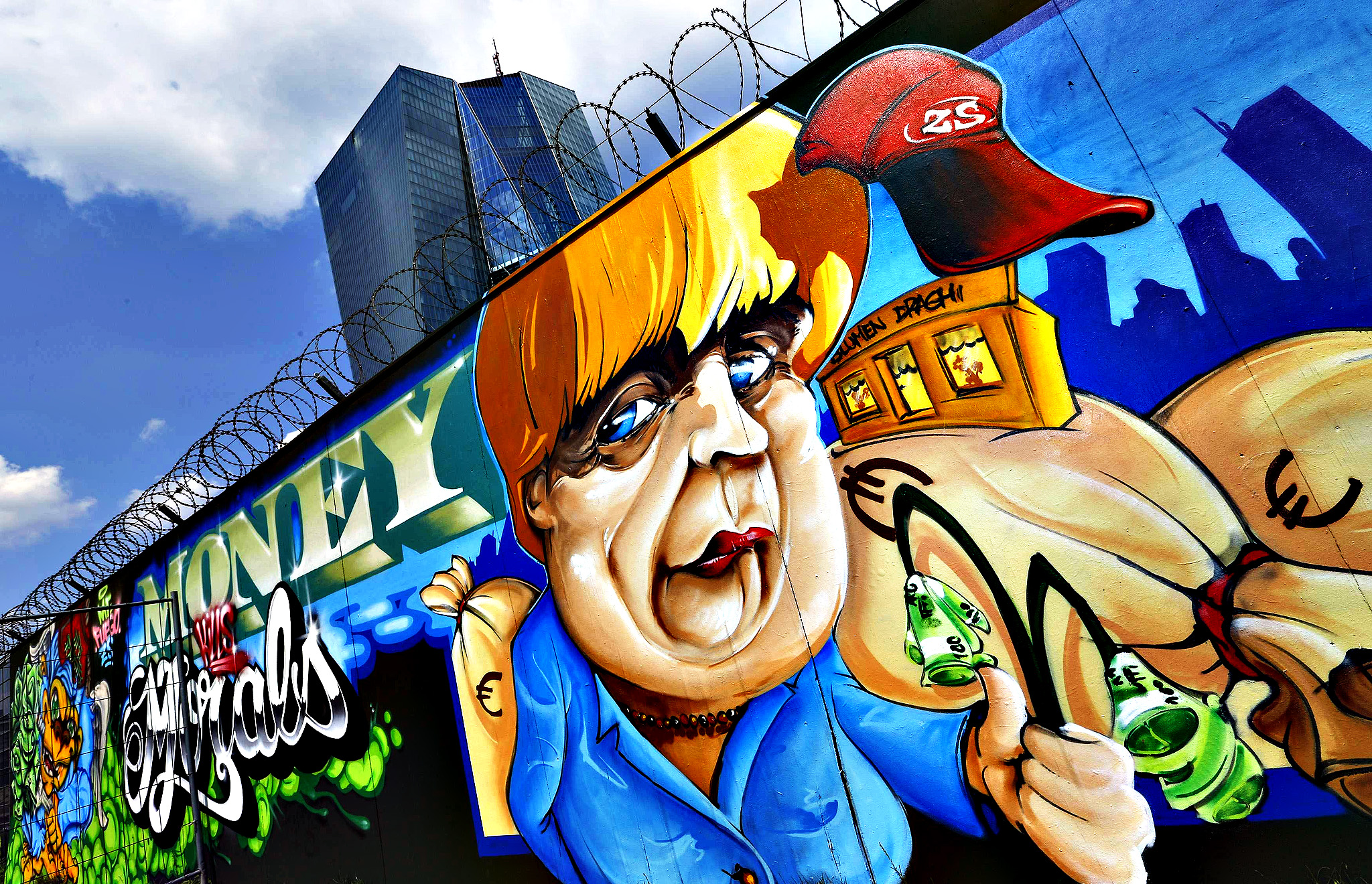"Graffiti depicting German Chancellor Angela Merkel and text reading ""Money vs Morals"" is sprayed on a fence surrounding the construction site for the new headquarters of the European Central Bank (ECB) in Frankfurt, August 6, 2014. The ECB council will hold its monthly meeting on Thursday."