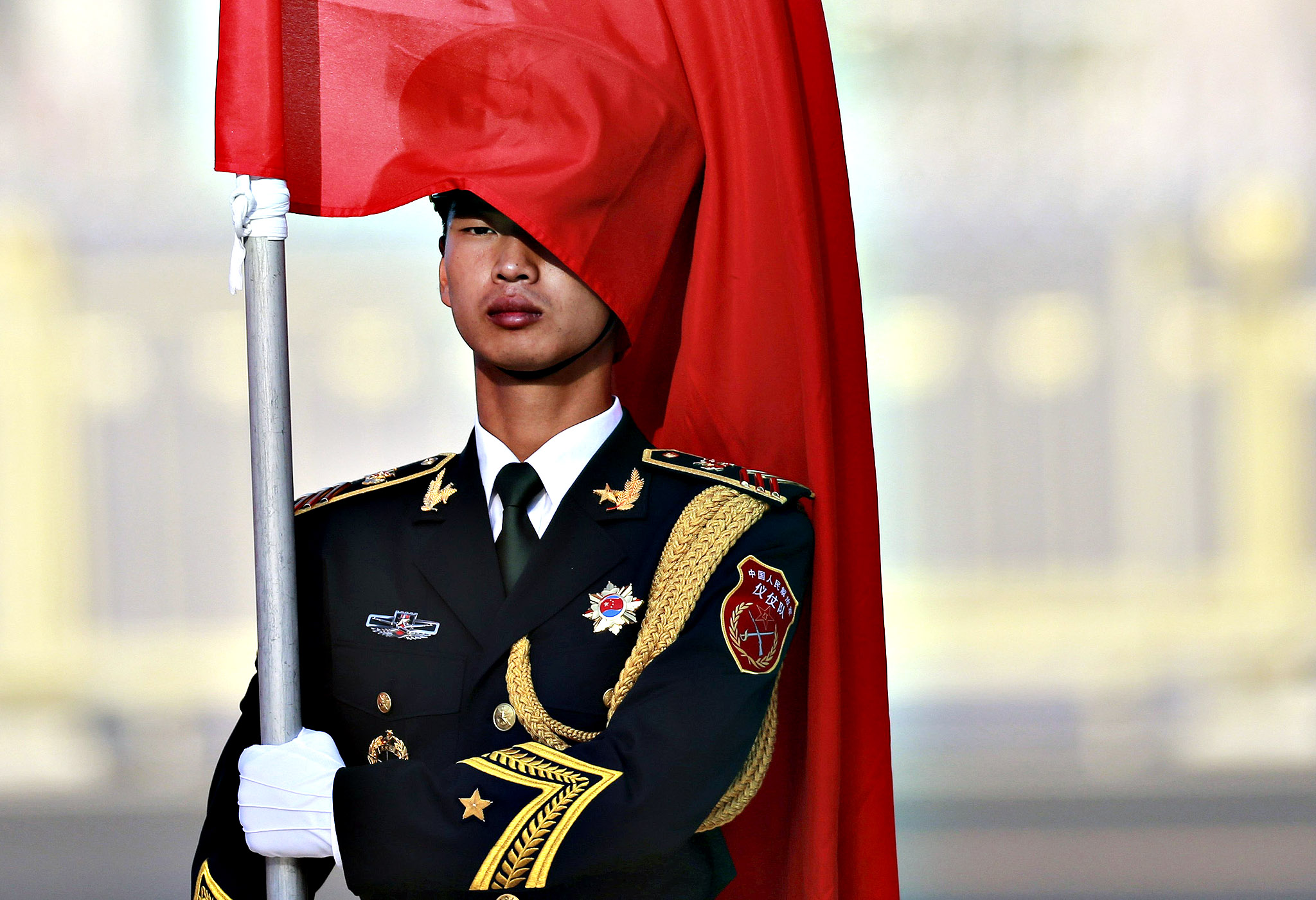 A member of the Chinese People's Liberation Army (PLA) honour guard stands with red flags during a welcoming ceremony for Prime Minister of Antigua and Barbuda Gaston Browne outside the Great Hall of the People in Beijing...A member of the Chinese People's Liberation Army (PLA) honour guard stands with red flags during a welcoming ceremony for Prime Minister of Antigua and Barbuda Gaston Browne outside the Great Hall of the People in Beijing, August 26, 2014.