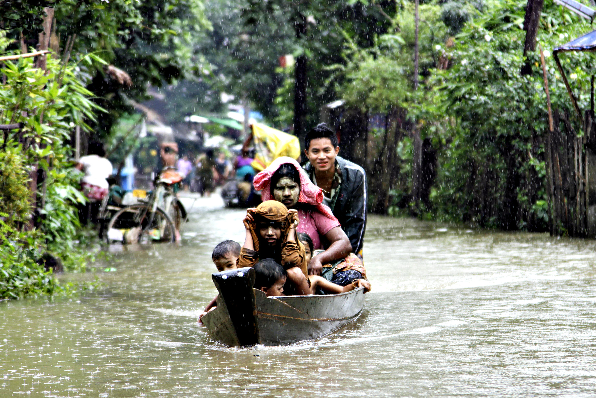 Local residents ride a boat on a flooded road overflown by the Bago river at a low-lying part in Bago, 80 kilometers (50 miles) northeast of Yangon, Myanmar, Monday, Aug. 4, 2014.   Flooding is common during Myanmar's monsoon season, which typically starts in late May and ends in mid-October.