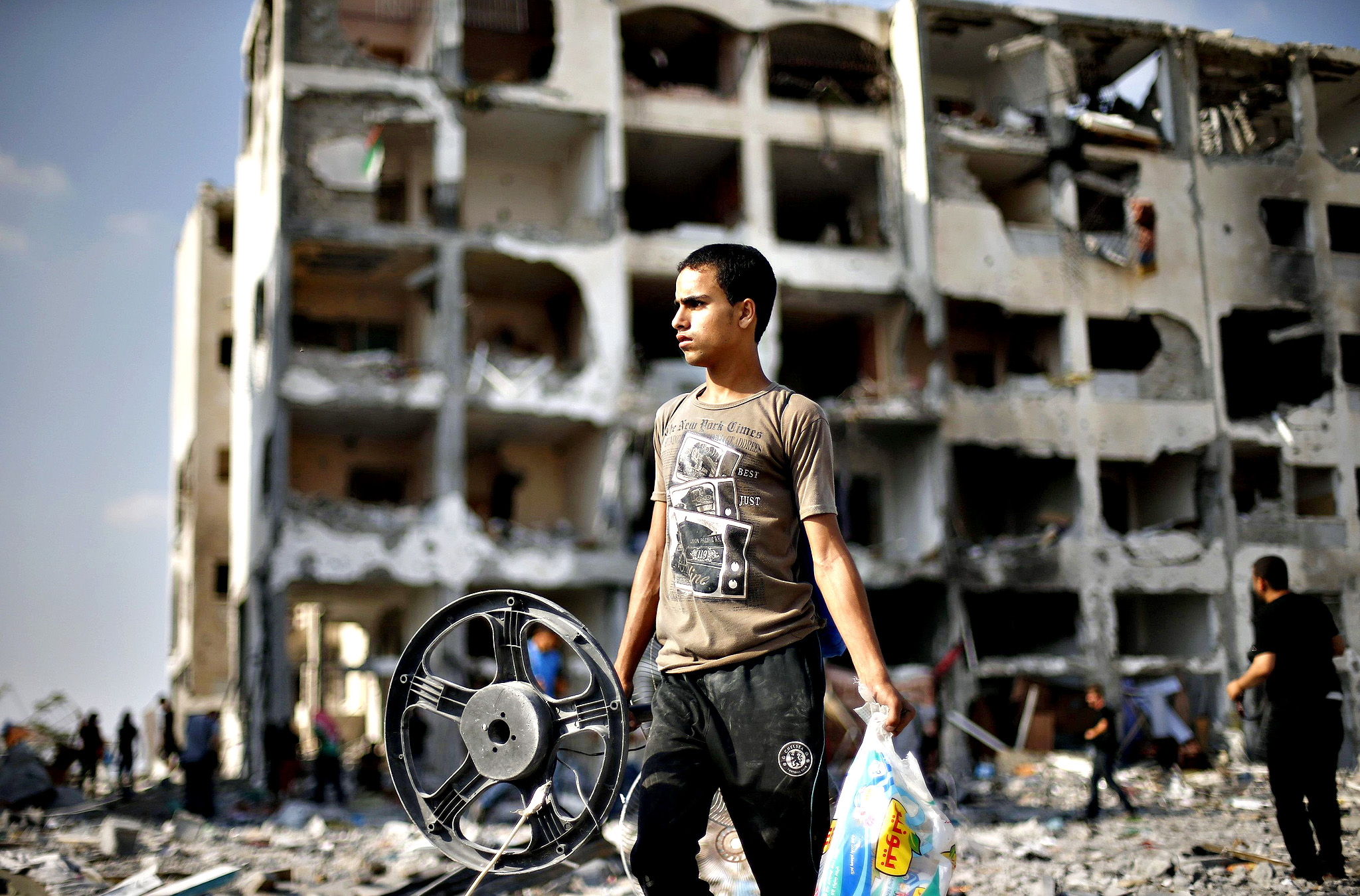 A Palestinian carries his belonging as he walks past a badly damaged residential building after returning to Beit Lahiya town in the northern Gaza Strip...A Palestinian carries his belonging as he walks past a badly damaged residential building after returning to Beit Lahiya town, which witnesses said was heavily hit by Israeli shelling and air strikes during the Israeli offensive, in the northern Gaza Strip August 5, 2014. Israel pulled its ground forces out of the Gaza Strip on Tuesday and began a 72-hour truce with Hamas mediated by Egypt as a first step towards negotiations on a more enduring end to the month-old war. Gaza officials say the war has killed 1,834 Palestinians, most of them civilians. Israel says 64 of its soldiers and three civilians have been killed since fighting began on July 8, after a surge in Palestinian rocket launches.