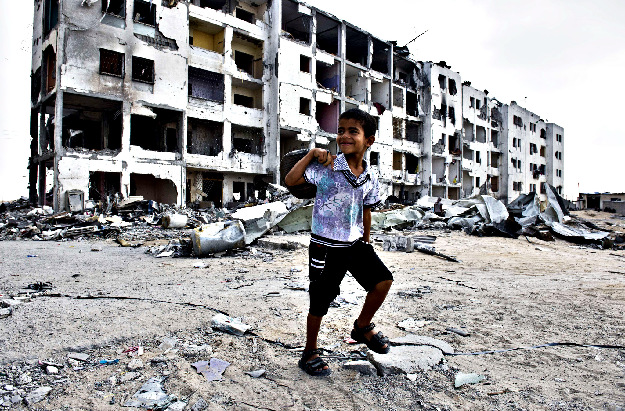 Palestinian boy Yussef, 8, smiles as he realises he is being photographed as he rounds a corner near shelled out apartment buildings while carrying bread to take back home to his father on August 14, 2014 in Beit Hanun, northern Gaza Strip. The other members of the family stay overnight at a UN school. Israel and Gaza militants were holding their fire today after a new truce got off to a shaky start, with night-time Palestinian rocket fire followed by Israeli air strikes.