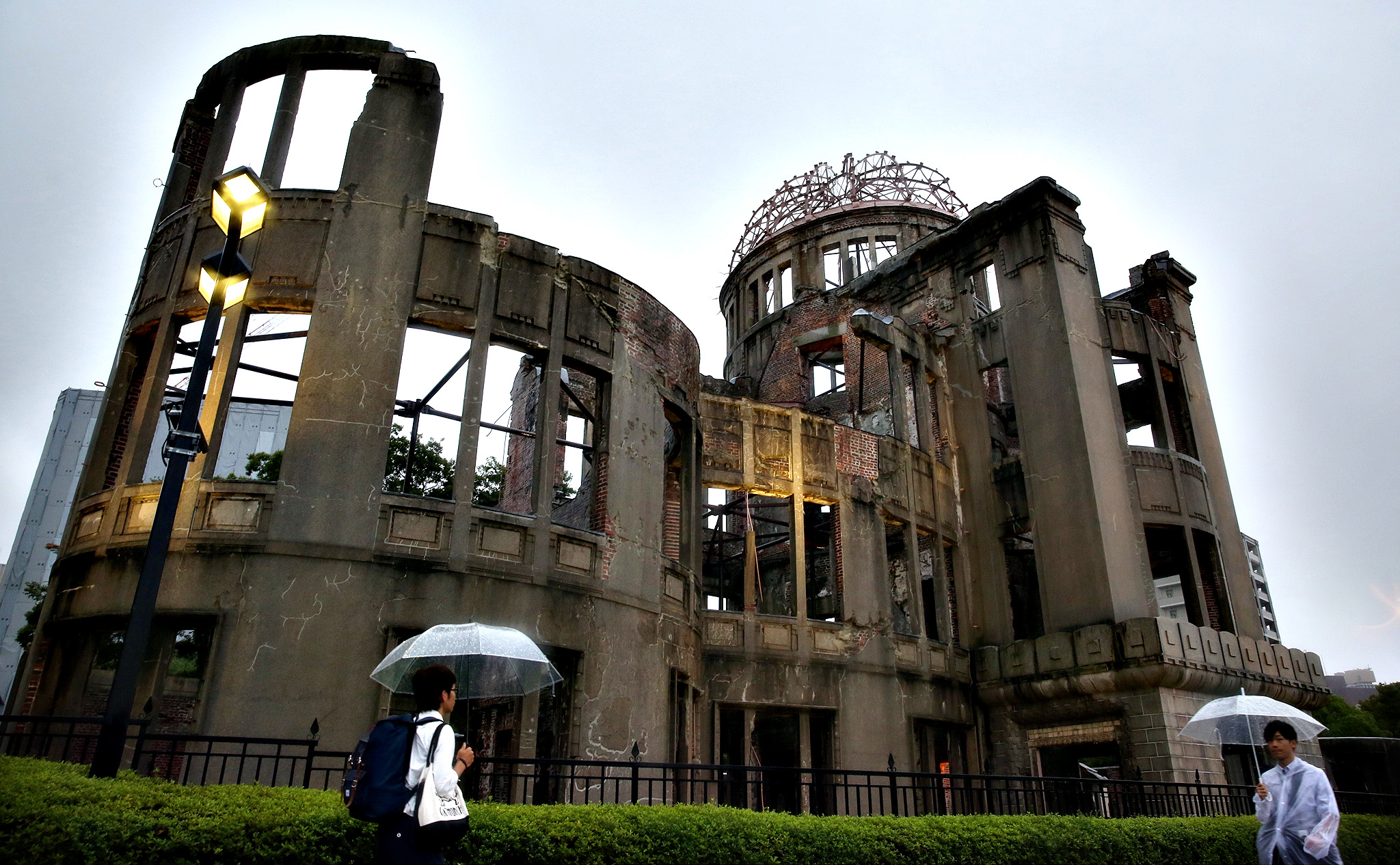 People walk in the rain in front of a Atomic Bomb Dome at the Hiroshima Peace Memorial Park on the day of the 69th anniversary of the atomic bombing of Hiroshima on August 6, 2014 in Hiroshima, Japan. Japan marks the 69th anniversary of the first atomic bomb that was dropped by the United States on Hiroshima on August 6, 1945, killing an estimated number of 70,000 people instantly with many thousands more dying over the following years from the effects of radiation. Three days later another atomic bomb was dropped on Nagasaki, ending World War II.
