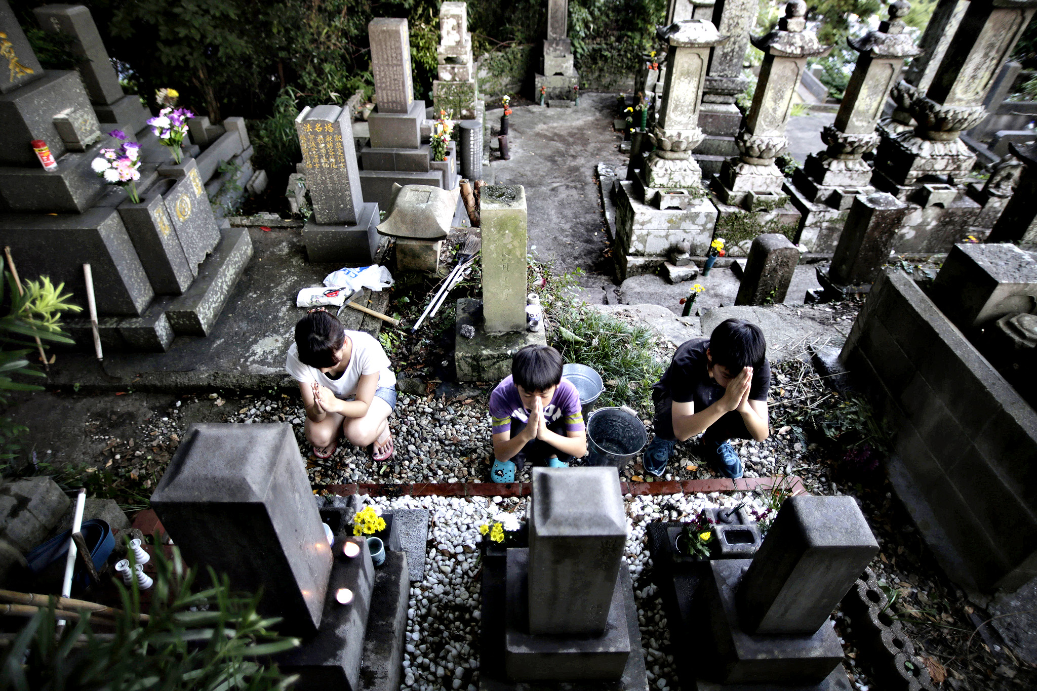 Children pray for their ancestors after sweeping their family tombstones at a cemetery in Haiki, Nagasaki Prefecture, southern Japan, Wednesday, Aug. 13, 2014 as they celebrate the Bon Festival. Japanese believe that their ancestors' spirits return to their homes to reunite with their family during the three-day festival starting Aug. 13.