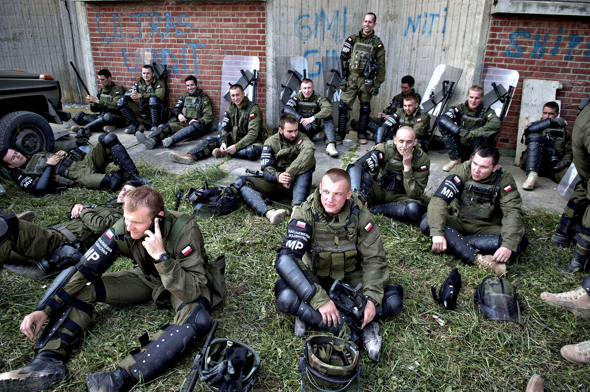 NATO-led Kosovo Force (KFOR) soldiers rest after taking part in a crowd and riot control exercise near the town of Ferizaj on August 29, 2014. Despite the deteriorating situation in the Middle East and Ukraine, NATO does not plan to reduce the number of its peacekeeping troops in Kosovo.
