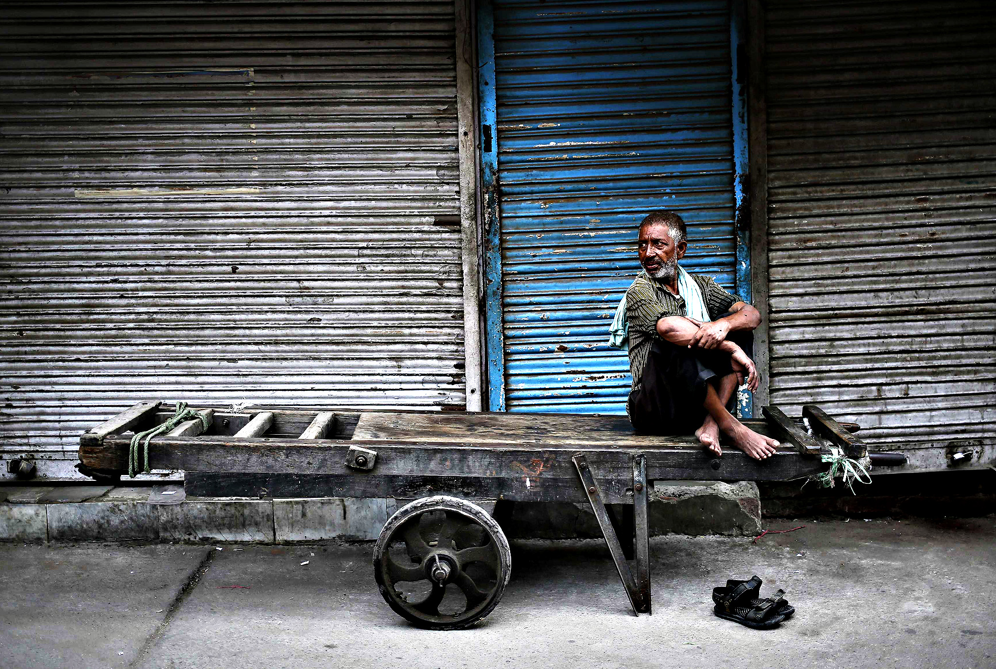 A migrant labourer sits on a handcart along a roadside in the old quarters of Delhi August 8, 2014.