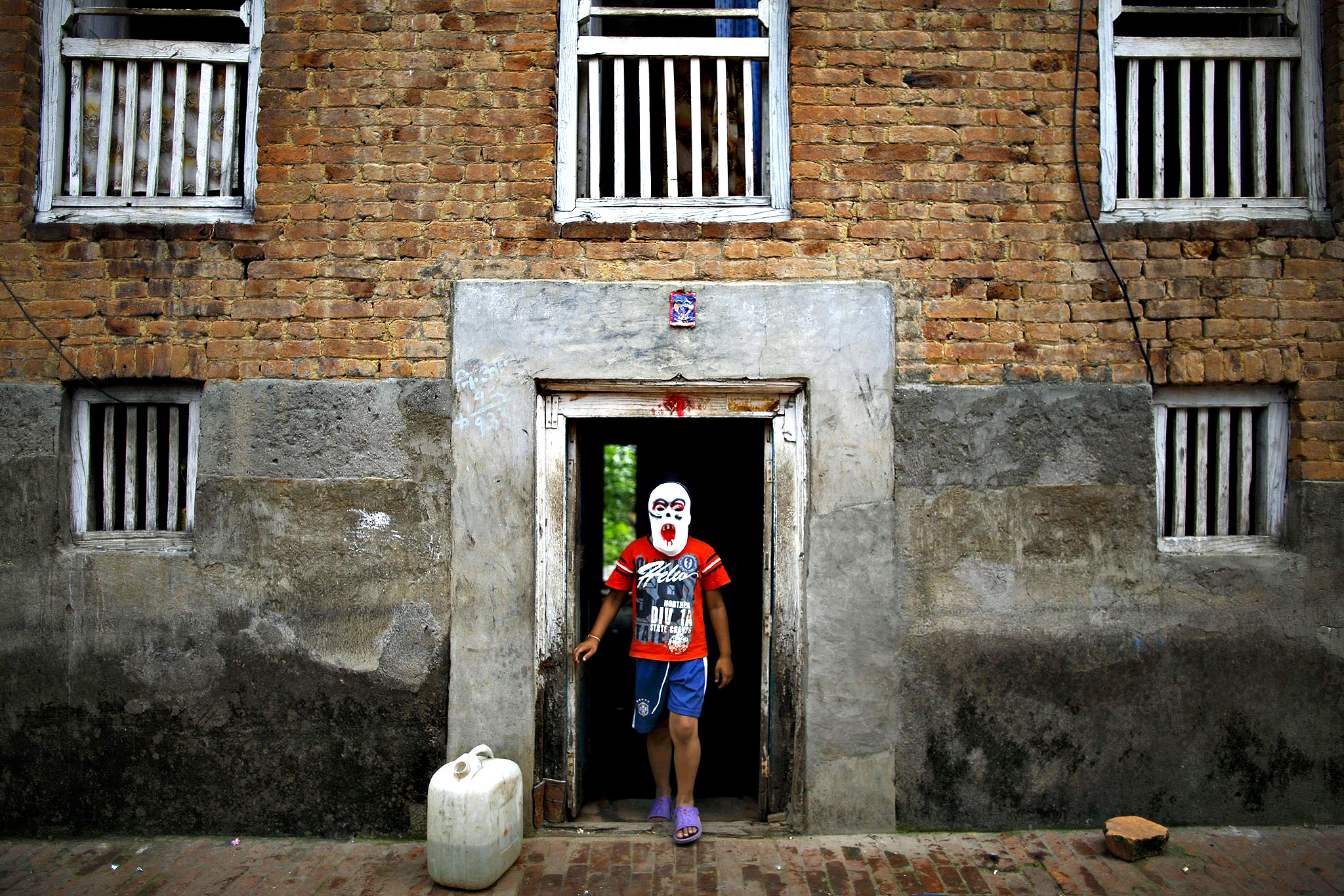 A masked devotee walks out from a house to take part in a parade commemorating the Neku Jatra-Mataya festival, the festival of lights, in Lalitpur August 12, 2014. Devotees celebrate the Buddhist festival which marks the victory of Sakyamuni Buddha over Mara, by praying for the souls of departed family members and holding parades throughout the city.