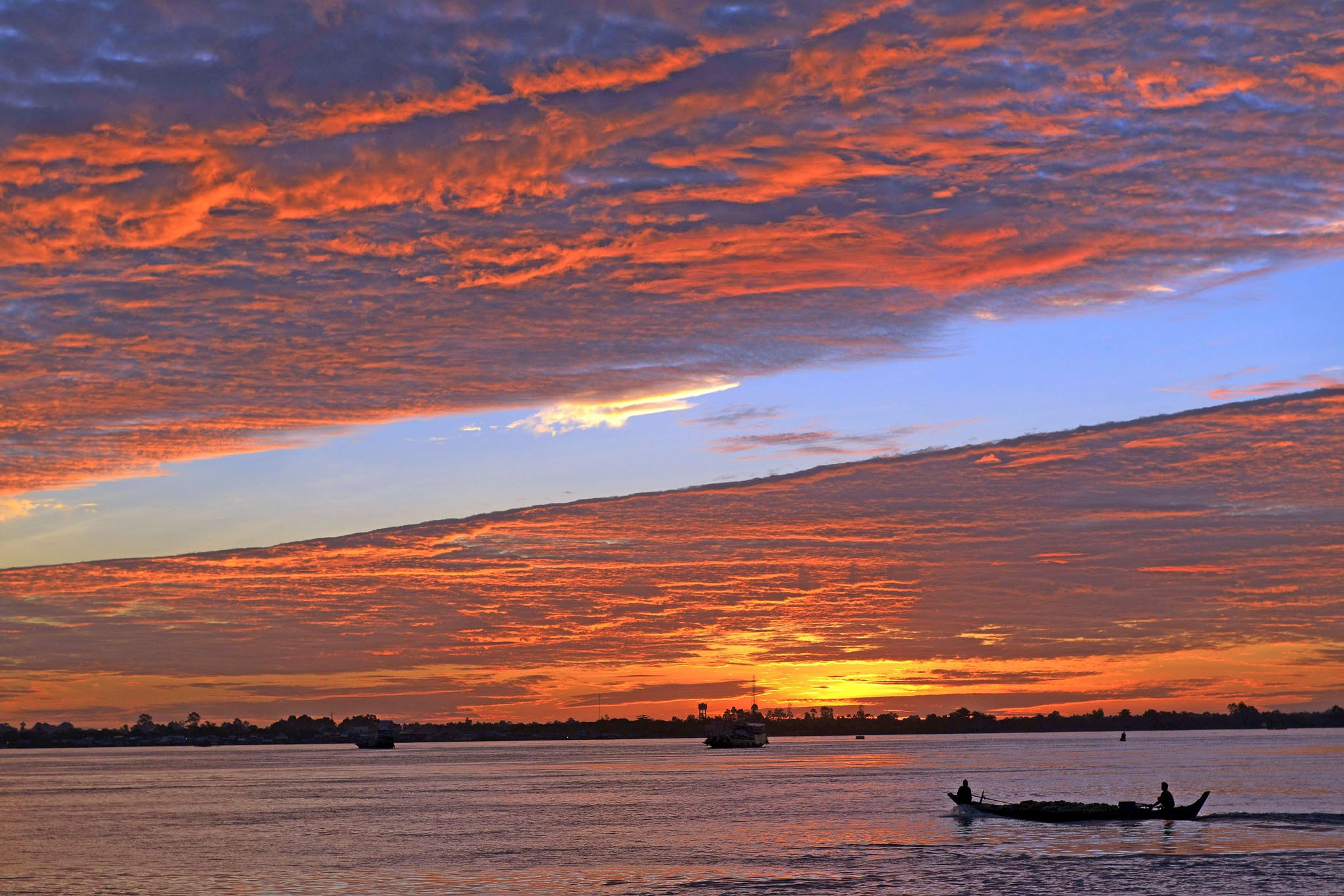 A boat commutes across the Mekong river