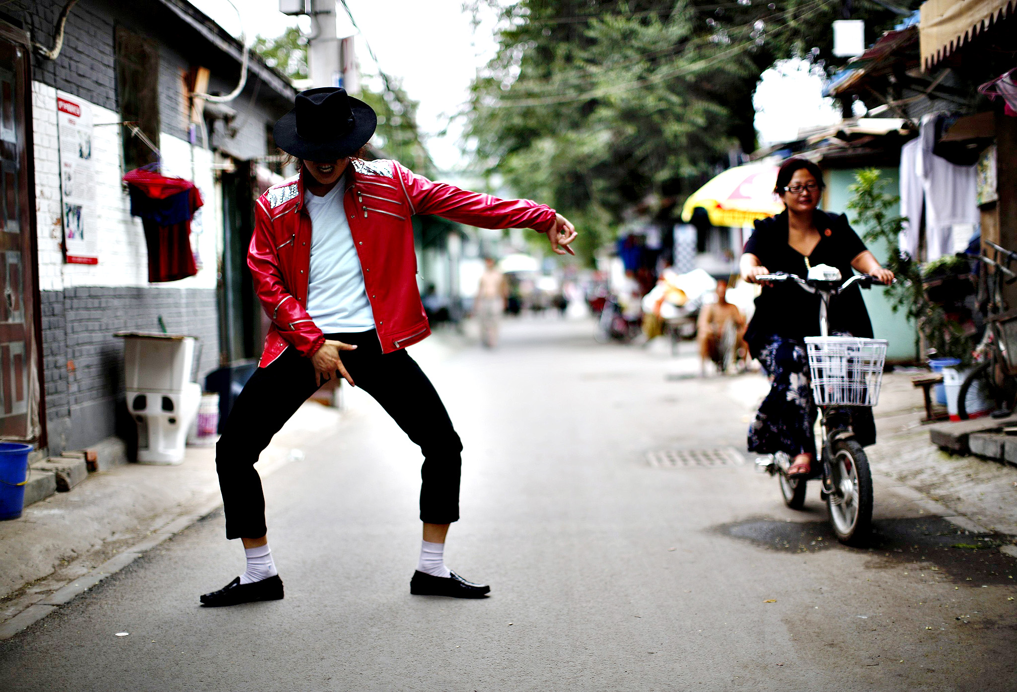 Zhang Guanhui, impersonating Michael Jackson, dances in front of his house located in a village for migrant workers during an interview with Reuters in Beijing...Zhang Guanhui, impersonating Michael Jackson, dances in front of his house located in a village for migrant workers during an interview with Reuters in Beijing. Zhang, born in 1984, quit elementary school and has since held jobs as a factory worker, waiter, and security guard. After watching a Michael Jackson music video four years ago for the first time, Zhang says he became fascinated and now puts on shows on the street and small stages impersonating the King of Pop.