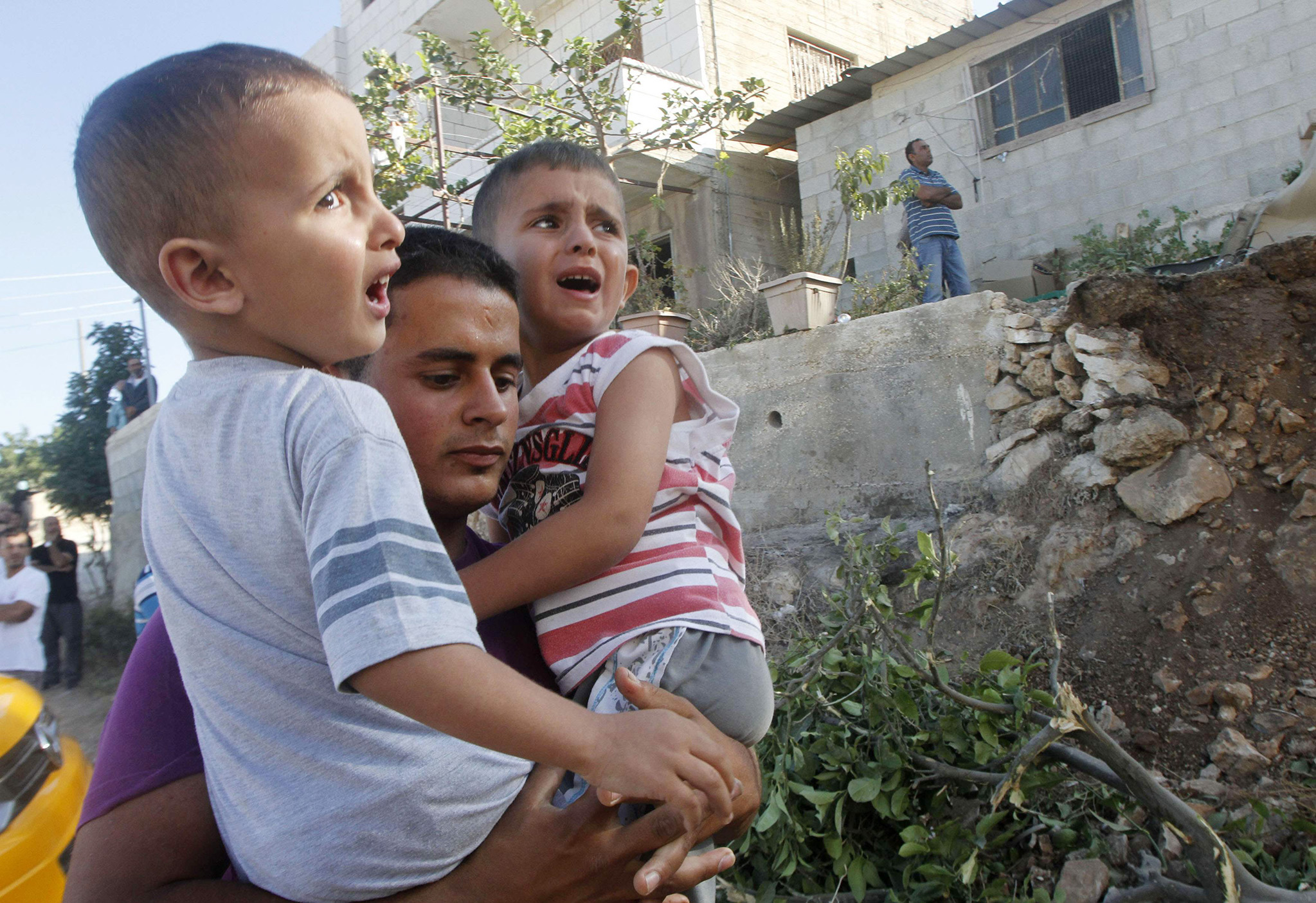 Palestinian boys are evacuated from their family's house, the house of Palestinian man Zakaria al-Aqra, following a raid by Israeli troops near Nablus
