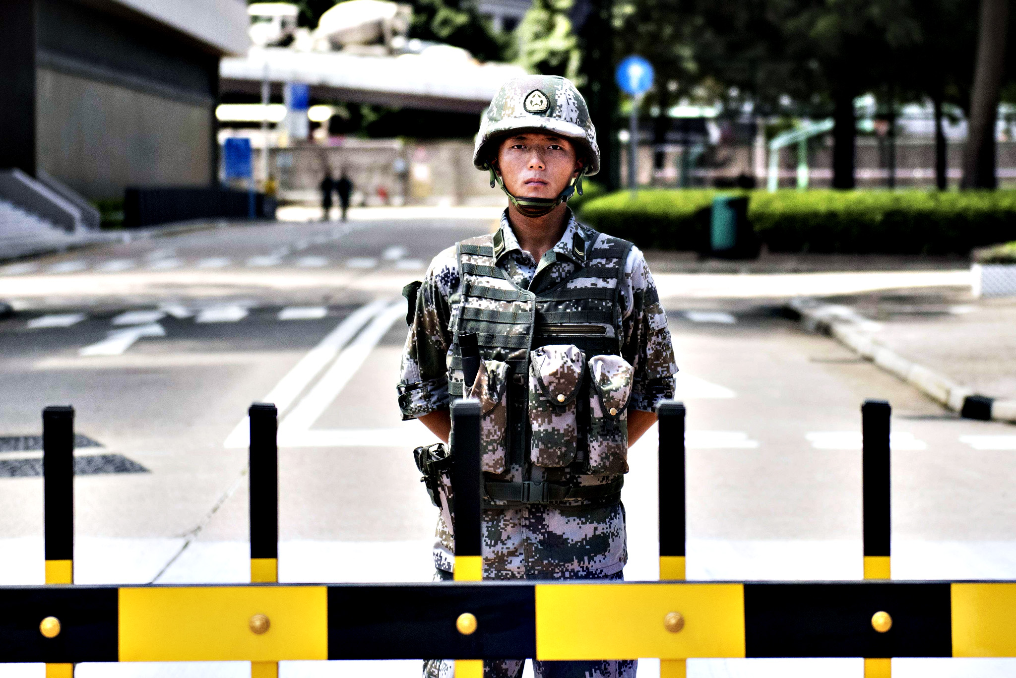 "A Chinese People's Liberation Army (PLA)...A Chinese People's Liberation Army (PLA) soldier stands guard at the entrance to the PLA's Hong Kong Garrison headquarters in Hong Kong on August 29, 2014.  Hong Kong residents expressed alarm on August 29 after Chinese army vehicles were photographed travelling down a major thoroughfare, in what democracy activists condemned as a show of ""military might"" ahead of expected protests."