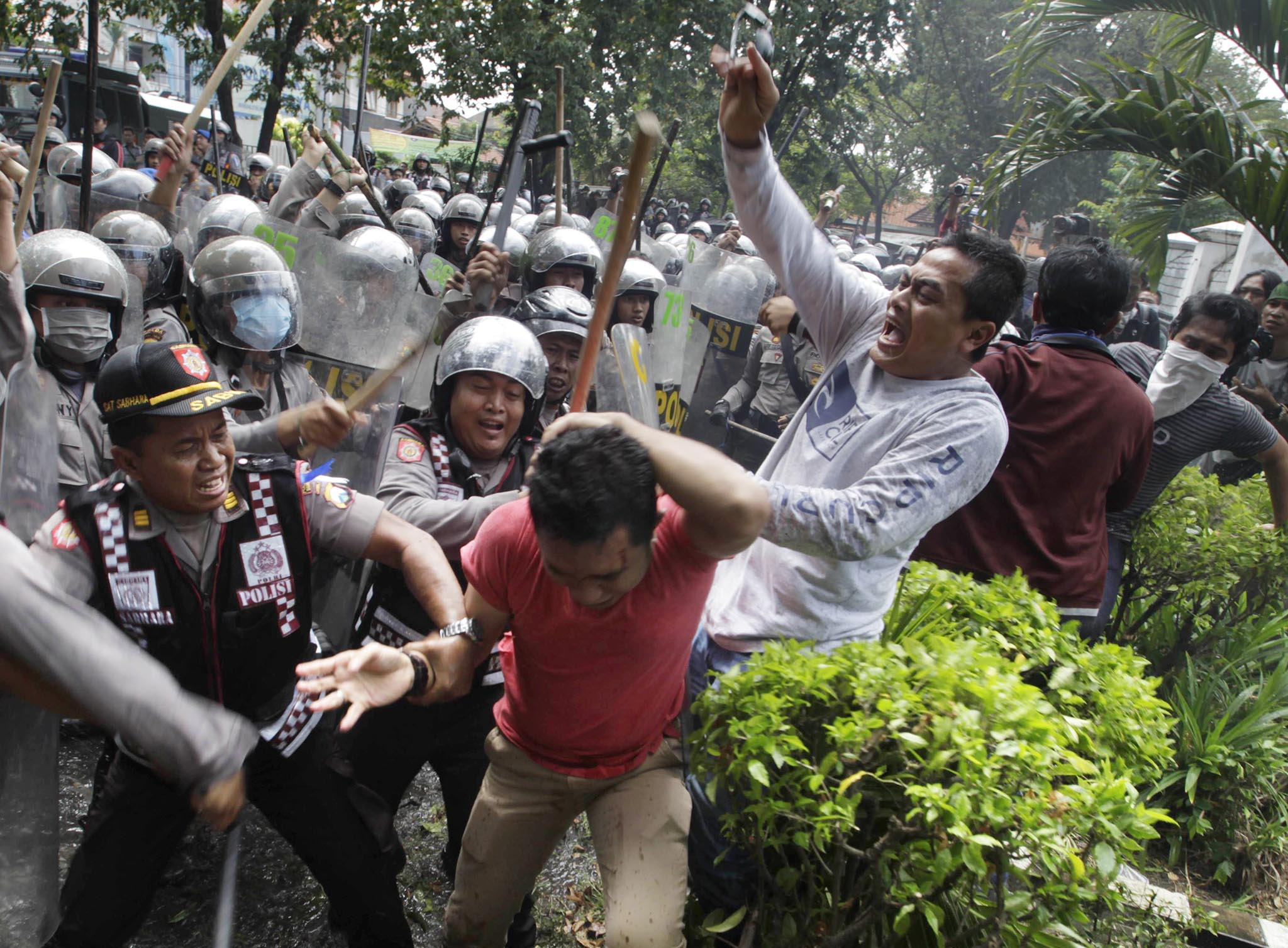 Police chase a supporter of Indonesia's losing presidential candidate Prabowo outside the General Election Commission office in Surabaya