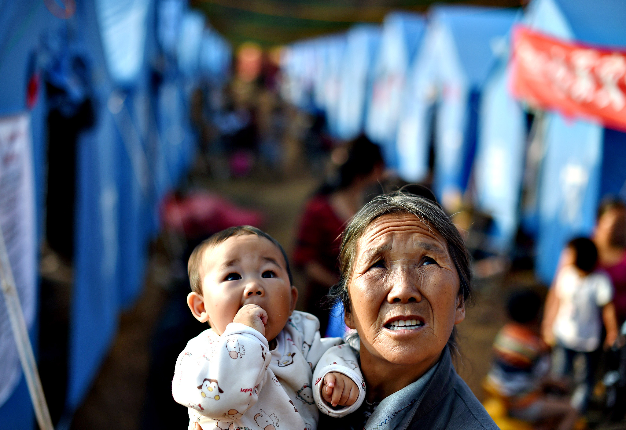 A woman and child watch a helicopter coming in to land near rows of tents housing earthquake survivors at Longtoushan, in China's southwest Yunnan province on August 6, 2014.  At least 589 people have died in the 6.1 magnitude earthquake that hit on August 3, officials said on August 6, marking a sharp increase in the death toll.