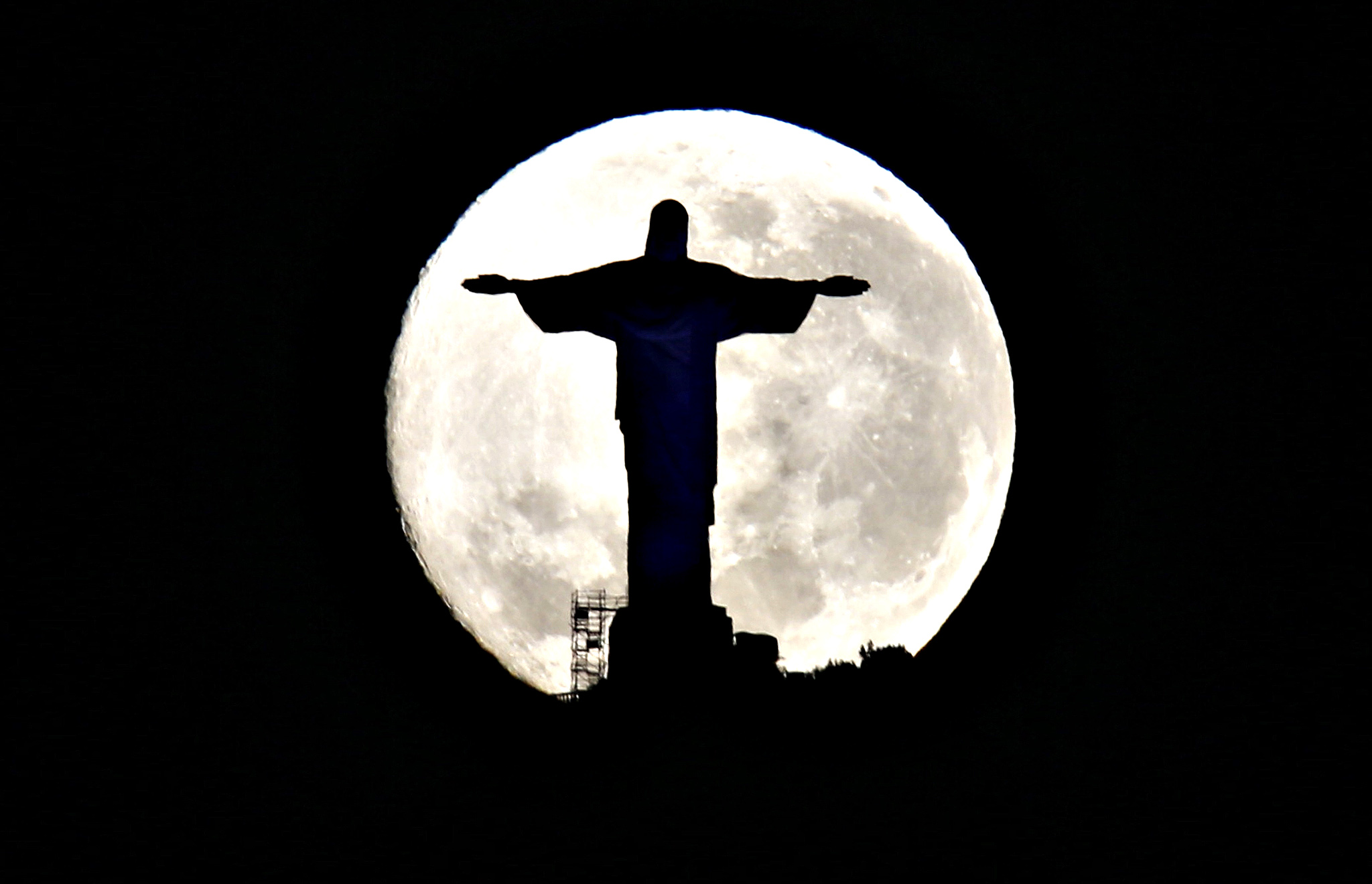 The super moon behind the Christ the Redeemer statue in Rio de Janeiro August 11, 2014. Occurring when a full moon or new moon coincides with the closest approach the moon makes to the Earth, the supermoon results in a larger-than-usual appearance of the lunar disk.
