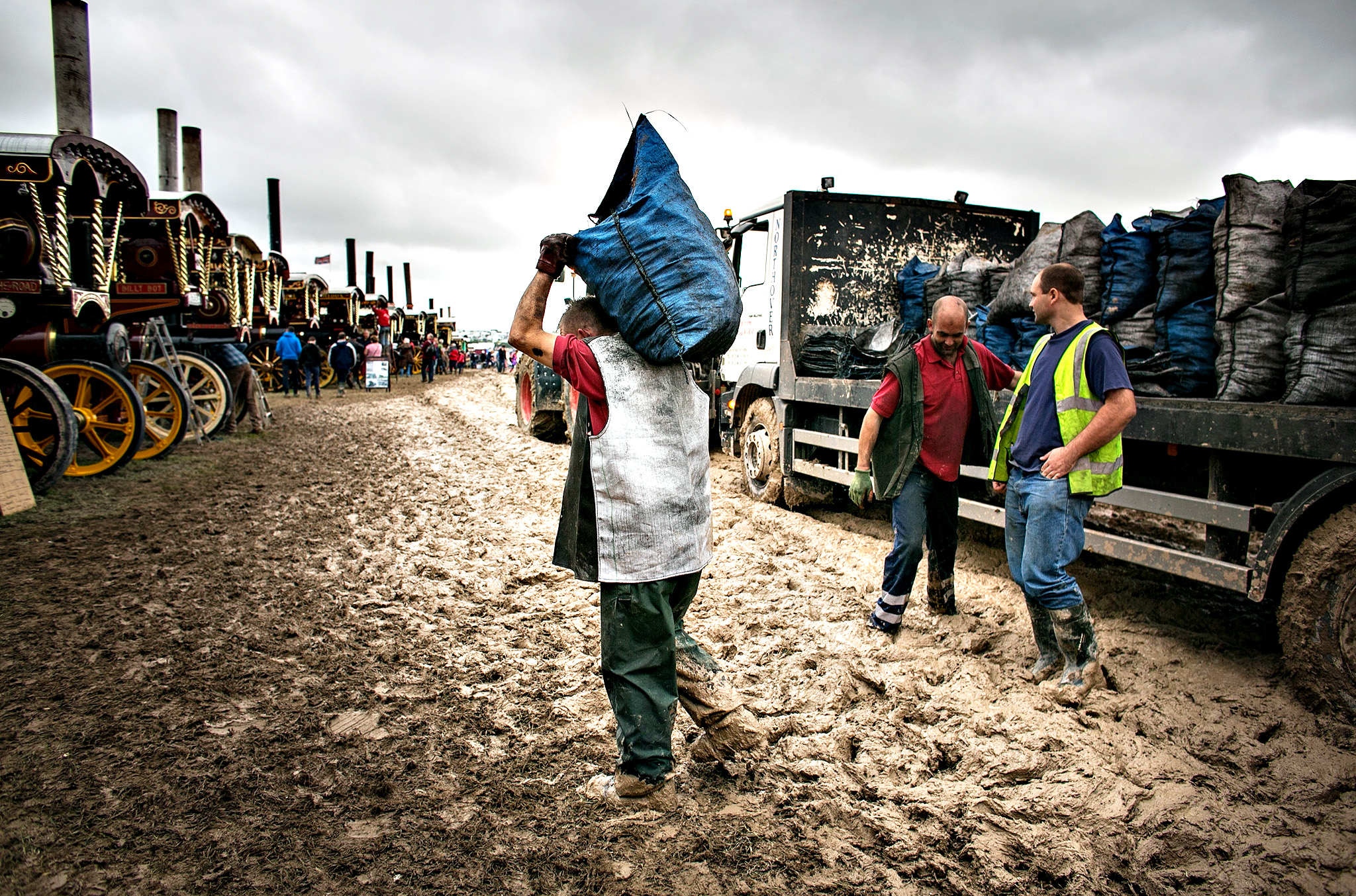 Coal man Simon Bee walks through the mud as he delivers bags of coal to showman's steam engines being prepared for display at the Great Dorset Steam Fair in Tarrant Hinton near Blandford on August 28, 2014 in Dorset, England. Heavy rain has disrupted the opening of the event, which is in its 45th year and regularly attracts 200,000 visitors to the site to see steam road locomotive, as well as other vintage vehicles.
