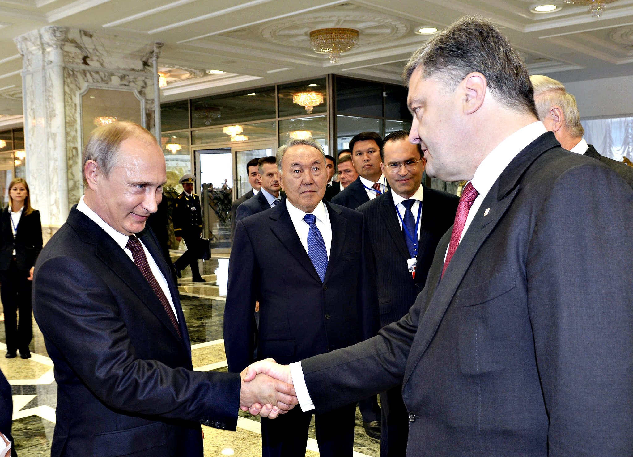 Russian President Vladimir Putin (L) shakes hands with his Ukrainian counterpart Petro Poroshenko, as Kazakh President Nursultan Nazarbayev (C) stands nearby, in Minsk August 26, 2014.