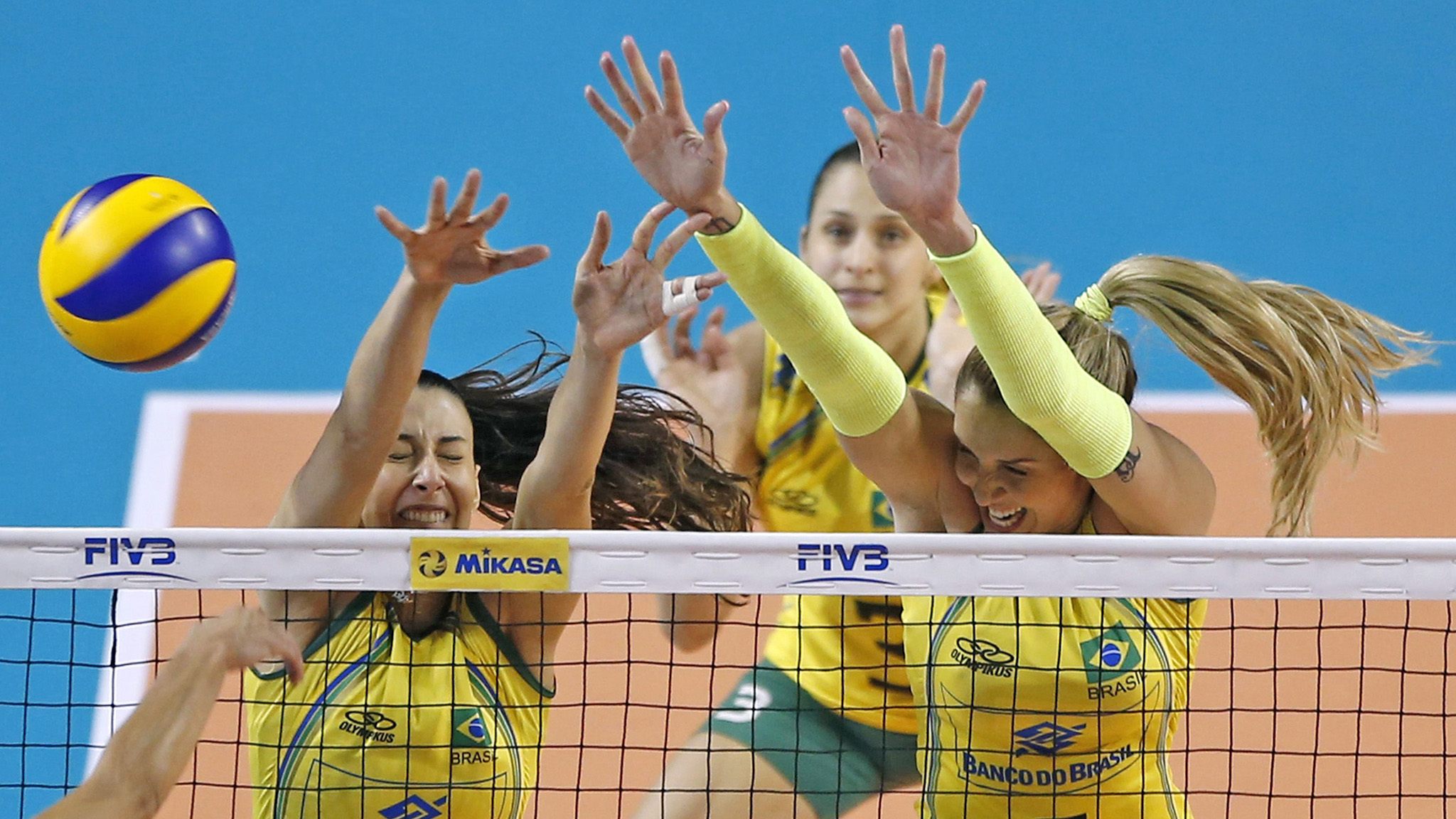 Sheilla Castro De Paula Blassioli and Thaisa Menezes of Brazil jump to block the ball spiked  by Gozde Sonsirma of Turkey during their FIVB Women's Volleyball World Grand Prix 2014 final round match in Tokyo