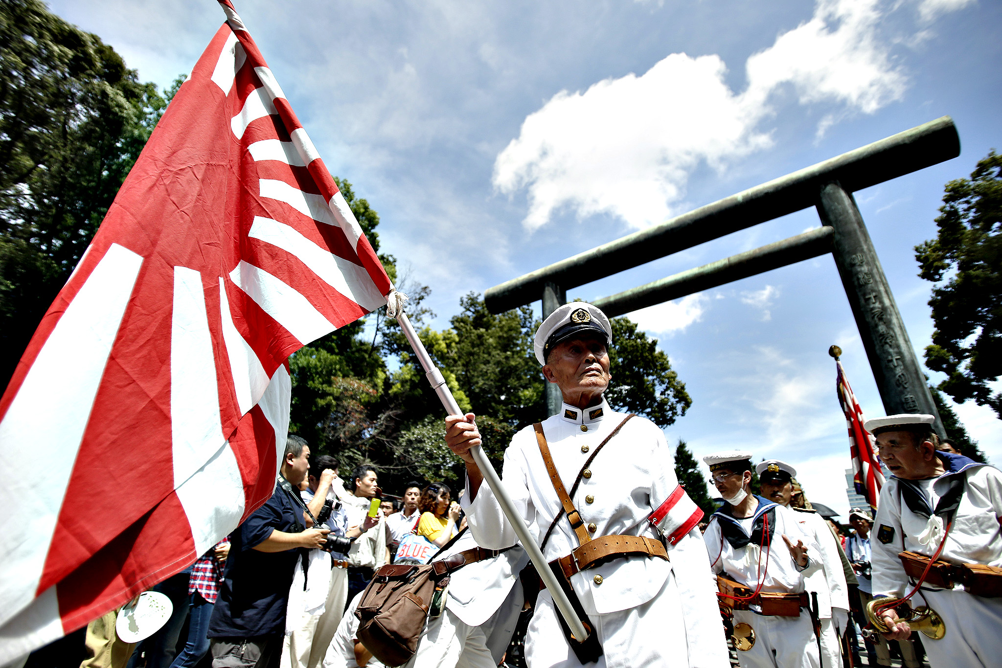A man dressed in a navy uniform holds Japan's rising sun flag at the Yasukuni Shrine in Tokyo, Japan, on Friday, Aug. 15, 2014. Japanese Prime Minister Shinzo Abe stayed away from the Tokyo war shrine on the 69th anniversary of Japan s World War II defeat today, instead sending a donation as he seeks a summit with Chinese President Xi Jinping.
