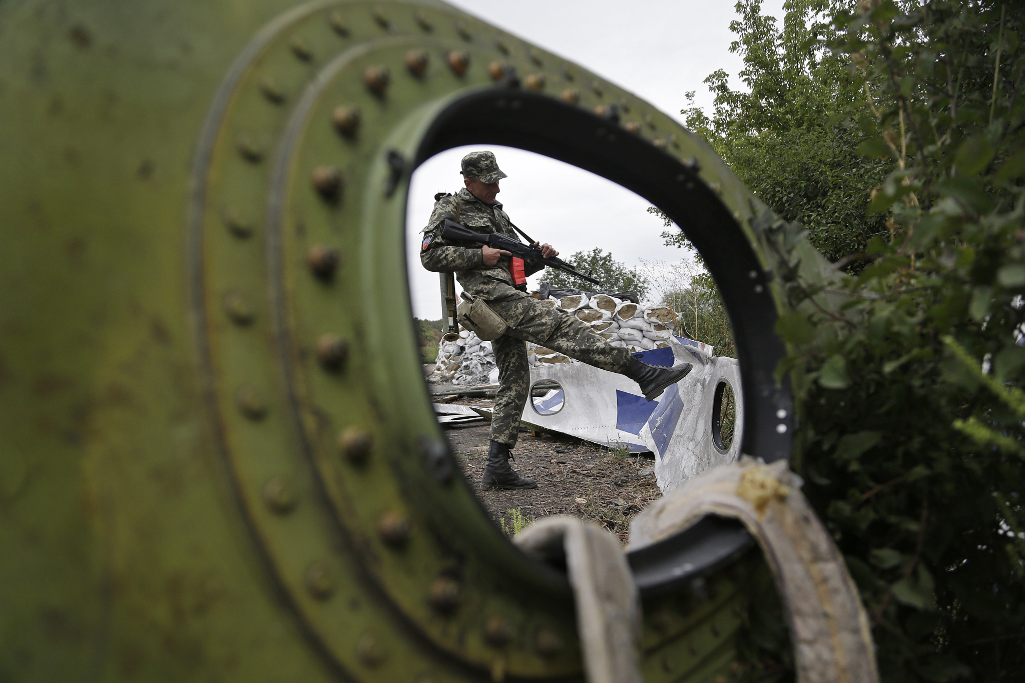 "A Pro-Russian rebel looks at pieces of the Malaysia Airlines Flight 17 plane near village of Rozsypne, eastern Ukraine, Tuesday, Sept. 9, 2014. The Dutch team investigating the downing of Malaysia Airlines Flight 17 over Eastern Ukraine says the crash was likely caused by the plane being hit by multiple ""high-energy objects from outside the aircraft."" The preliminary report published Tuesday by the Dutch Safety Board stopped short of saying the Boeing 777 was shot down by a surface-to-air missile, but its findings appear to point to that conclusion. (AP Photo/Sergei Grits)"