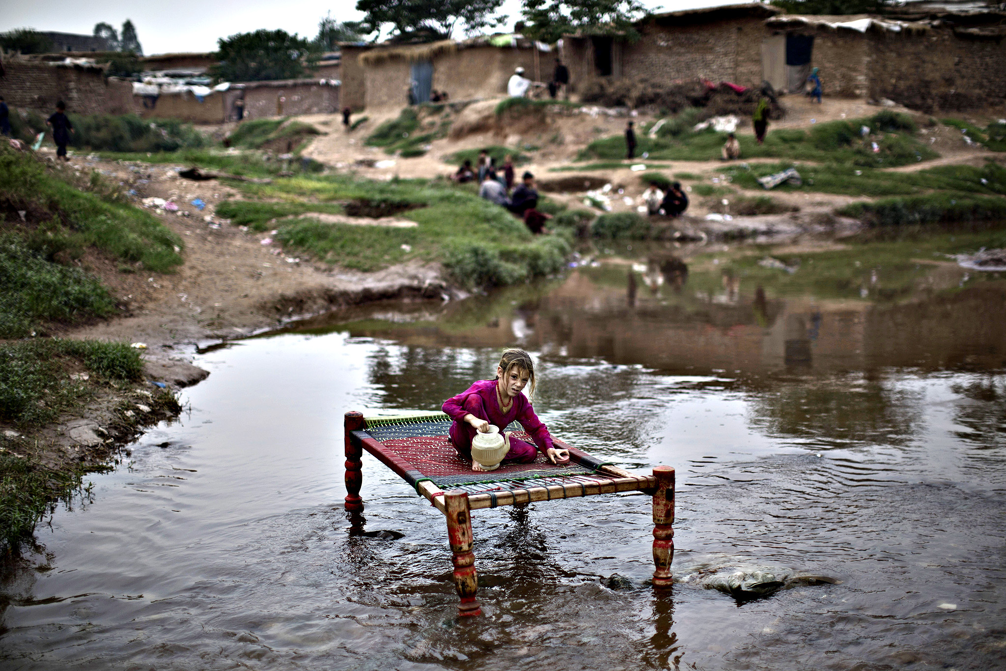 An Afghan refugee girl washes a bed in a polluted stream, in a poor neighborhood on the outskirts of Islamabad, Pakistan, Tuesday, Sept. 30, 2014.