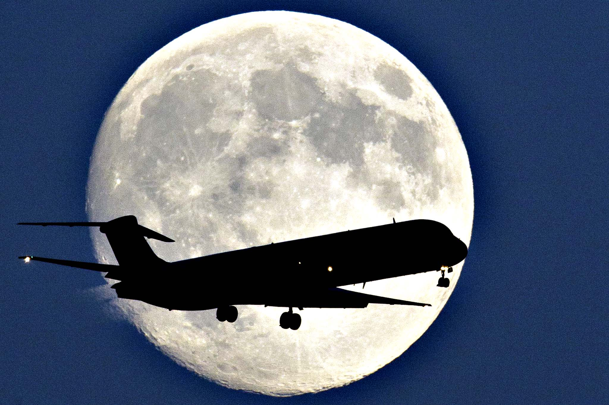 "An airplane passes a nearly full moon as it makes its approach to Philadelphia International Airport, in Philadelphia. Monday night's full moon, also known as a Harvest Moon, will be the third and final ""supermoon"" of 2014. The phenomenon, which scientists call a ""perigee moon,"" occurs when the moon is near the horizon and appears larger and brighter than other full moons."