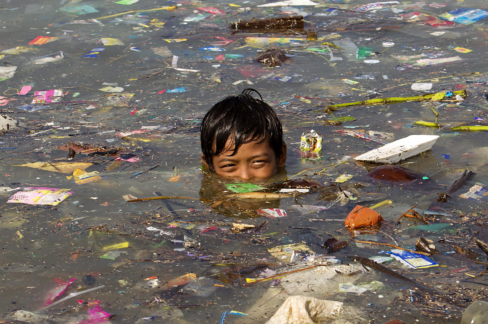A Filipino boy swims among washed up rubbish in Manila bay, the Philippines, 23 September 2014. Countries and organizations began to announce measures to reduce greenhouse gas emissions and divest in fossil fuels on the one-day UN Climate Summit, where more pledges to reduce climate change are expected. Addressing the controversial issue of taxing or trading in carbon emissions, the World Bank on 22 September 2014, identified at least 73 countries that advocate putting a price on the release of carbon dioxide into the atmosphere. They represent a combined 54 per cent of global greenhouse gas emissions blamed for global warming, and include major emitters China, Russia and members of the European Union, emerging markets Indonesia, Mexico and South Africa, and vulnerable island countries including the Philippines, Kiribati and Nauru.  EPA/RITCHIE B. TONGO