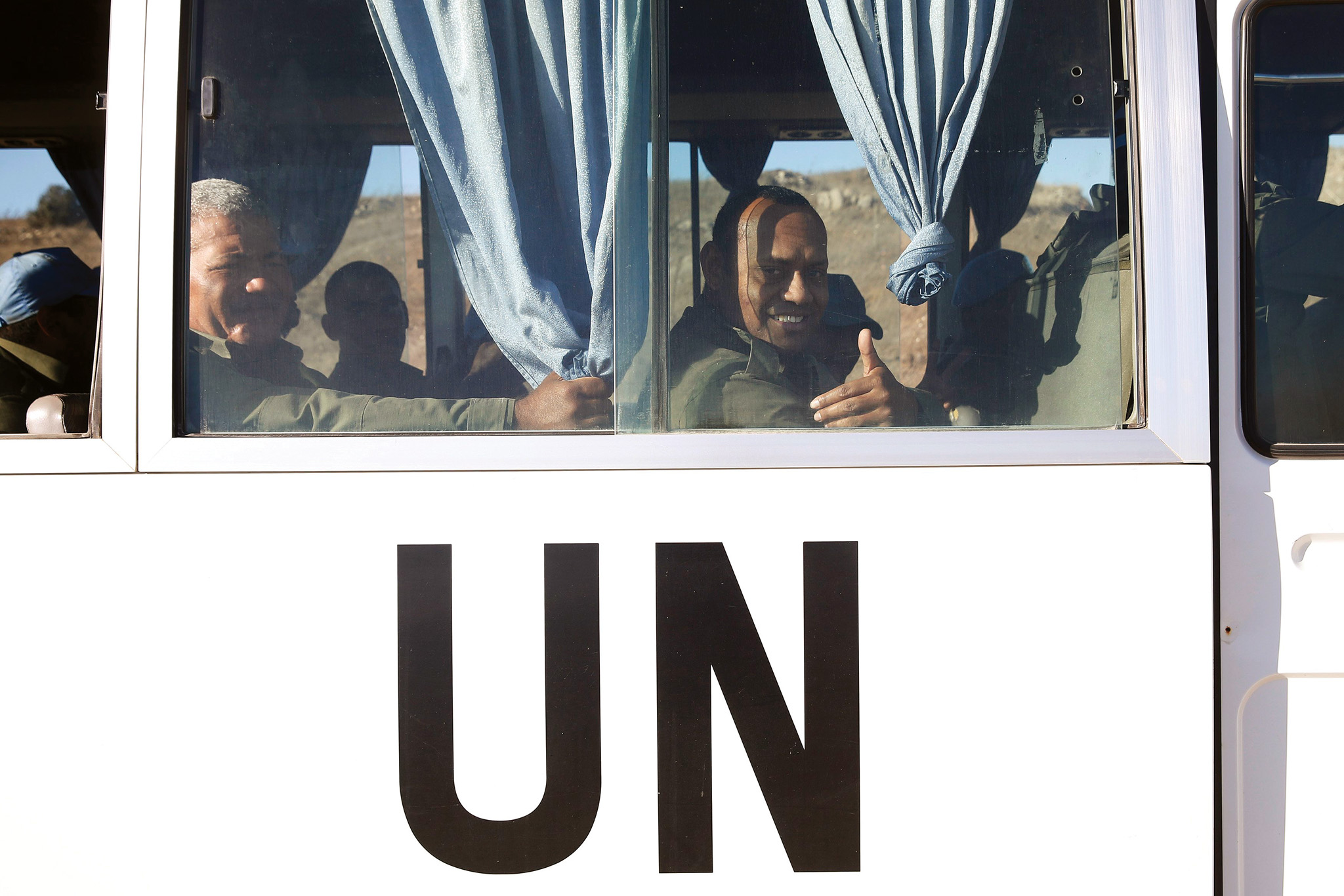 Fijian U.N. peacekeepers released by al-Qaeda-linked group Nusra Front in Syria on Thursday, gesture from inside a vehicle as they arrive in Israeli-held territory on the Golan heights...Fijian U.N. peacekeepers released by al-Qaeda-linked group Nusra Front in Syria on Thursday, gesture from inside a vehicle as they arrive in Israeli-held territory on the Golan heights September 11, 2014. The peacekeepers were taken hostage two weeks ago when several Islamist militant groups including Nusra attacked in the volatile frontier between Syria and Israel. REUTERS/Baz Ratner (POLITICS CIVIL UNREST CONFLICT)