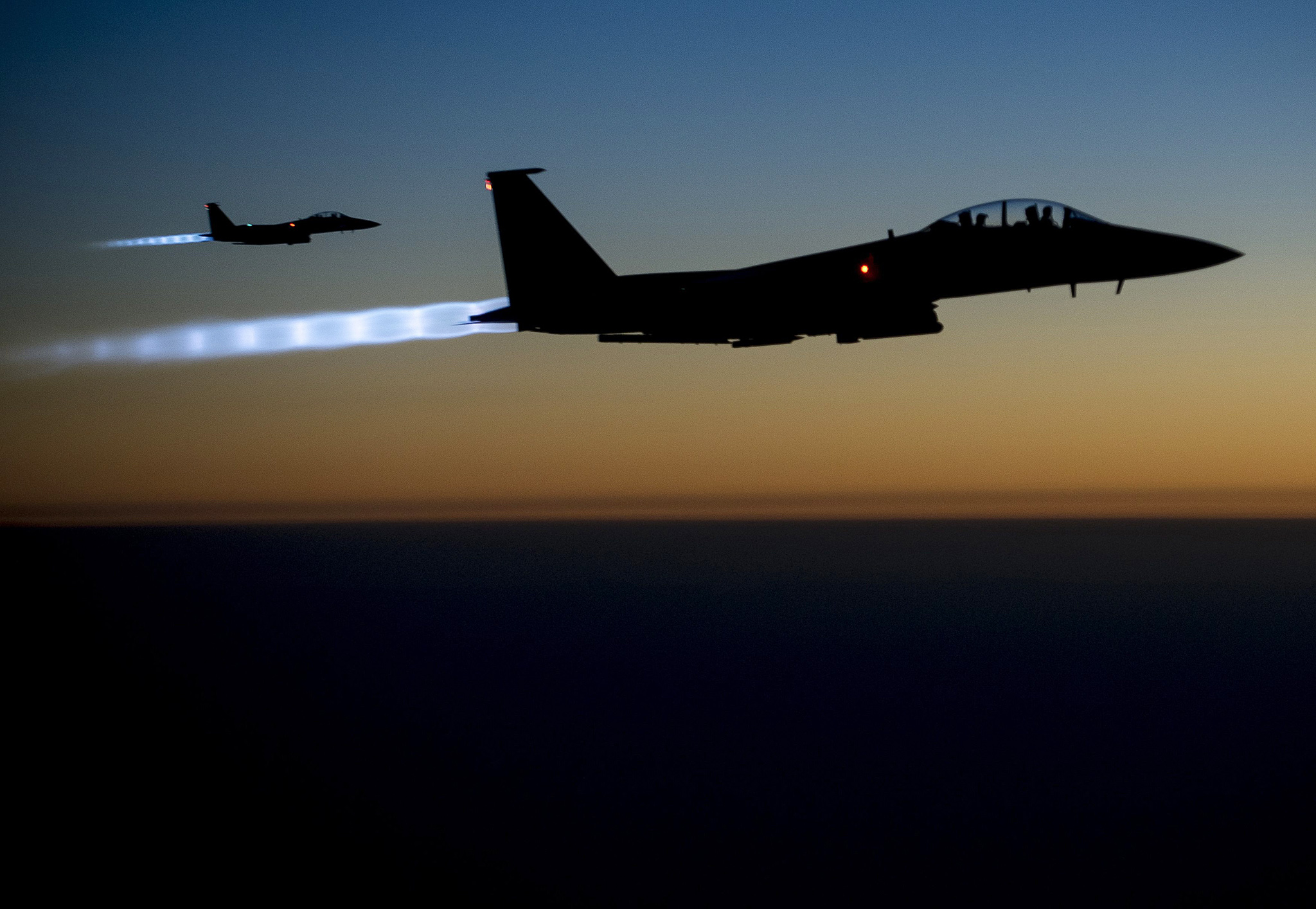 A pair of U.S. Air Force F-15E Strike Eagles fly over northern Iraq...A pair of U.S. Air Force F-15E Strike Eagles fly over northern Iraq after conducting airstrikes in Syria, in this U.S. Air Force handout photo taken early in the morning of September 23, 2014. These aircraft were part of a large coalition strike package that was the first to strike ISIL targets in Syria. At least 14 Islamic State fighters were killed in air strikes by U.S.-led forces overnight in northeast Syria, a group monitoring the war said on September 25, 2014, and the Syrian air force bombed rebel areas in the west of the country. REUTERS/U.S. Air Force/Senior Airman Matthew Bruch/Handout  (IRAQ - Tags: POLITICS CONFLICT TPX IMAGES OF THE DAY) FOR EDITORIAL USE ONLY. NOT FOR SALE FOR MARKETING OR ADVERTISING CAMPAIGNS. THIS IMAGE HAS BEEN SUPPLIED BY A THIRD PARTY. IT IS DISTRIBUTED, EXACTLY AS RECEIVED BY REUTERS, AS A SERVICE TO CLIENTS.