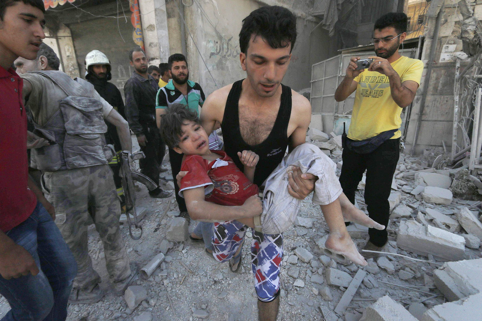 Man carries an injured child after what activists said were barrel bombs were dropped by forces of Syria's President Assad in Aleppo's al-Saliheen district