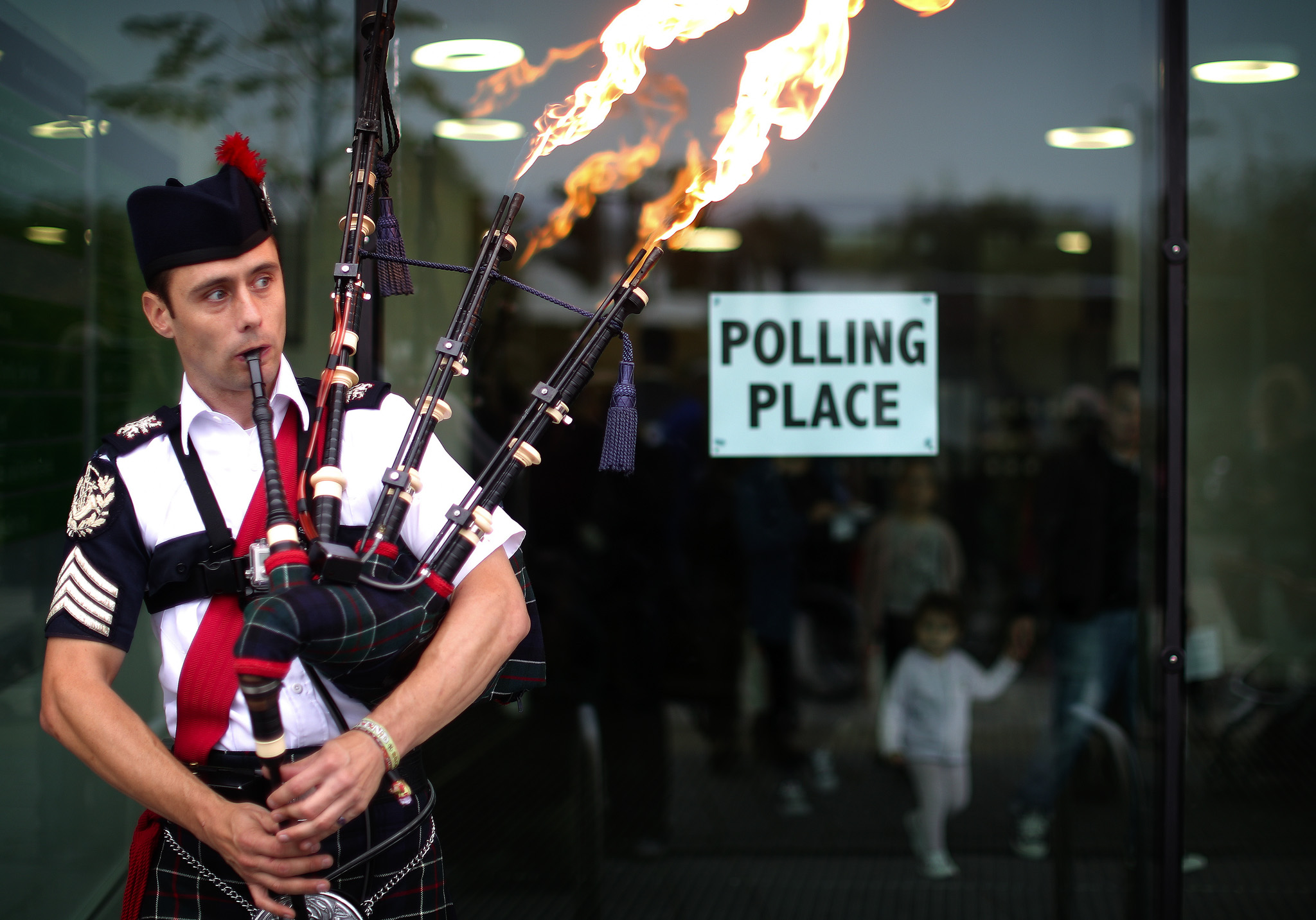 Piper, Ryan Randall, leads a march to the polling station in Craigmillar, Edinburgh.