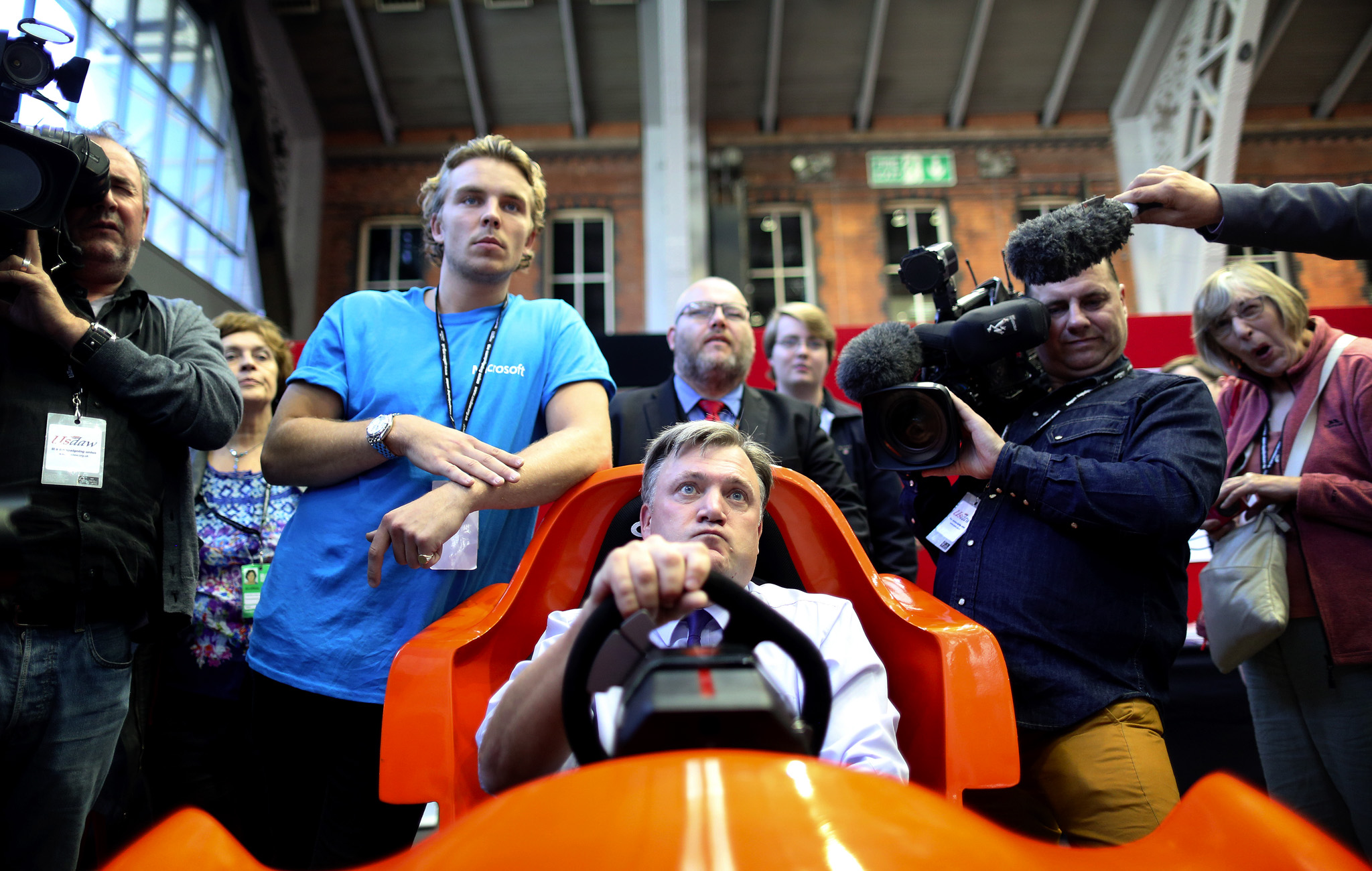 Shadow Chancellor, Ed Balls, takes part in a driving game on a stand in the conference hall at the Labour party conference in Manchester