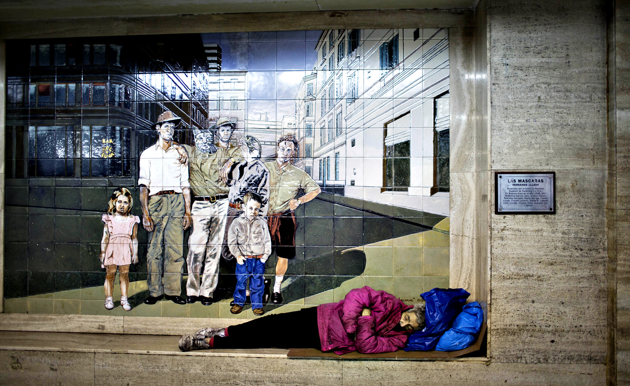 A woman sleeps in front of a painting decorating a subway station in Buenos Aires, Argentina, Wednesday, Sept. 17, 2014.