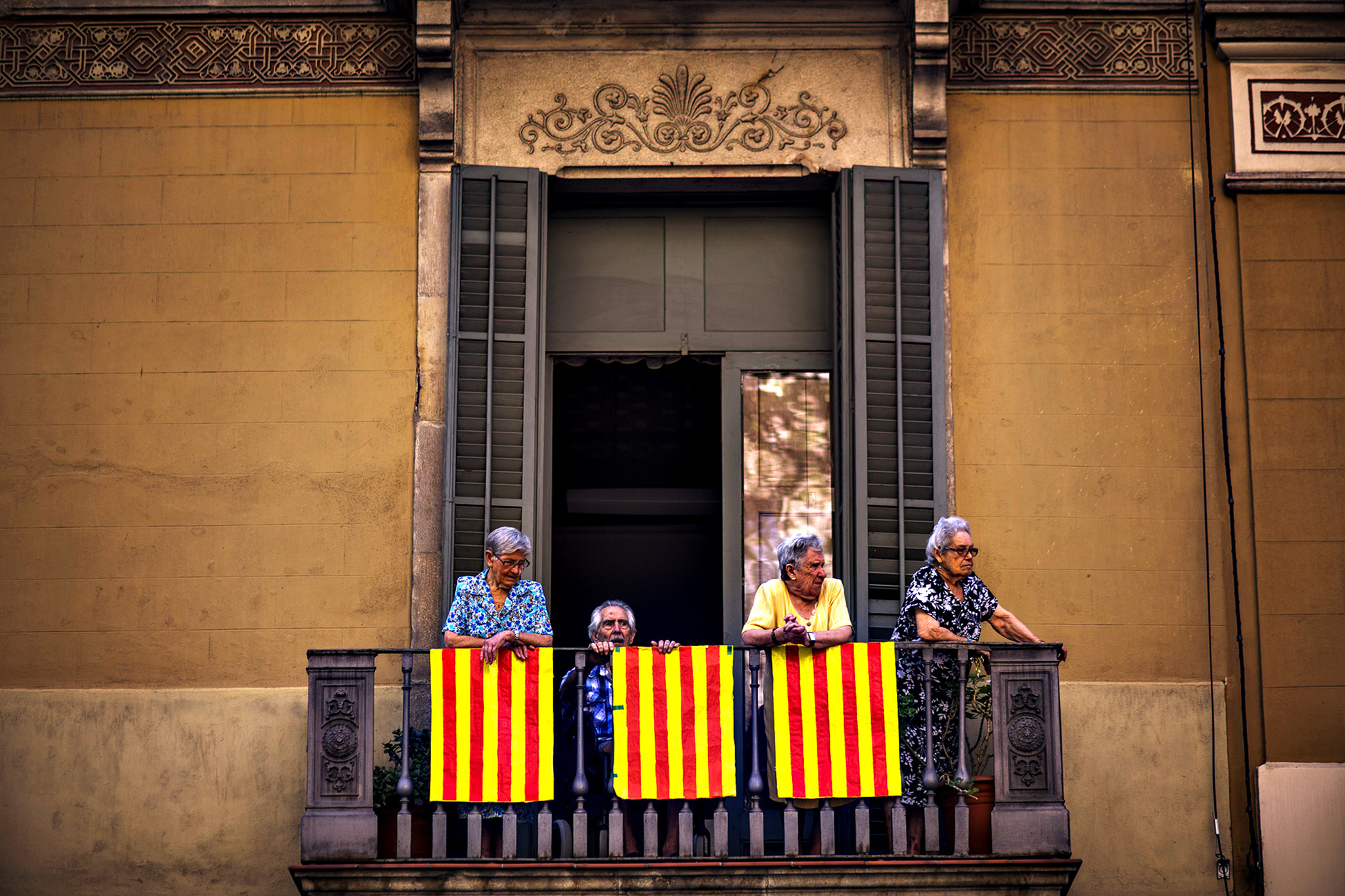 People stand on a balcony decorated with Catalonia flags in Barcelona, Spain, Thursday, Sept 11, 2014. A week before Scotland votes on whether to break away from the United Kingdom, separatists in northeastern Spain were trying to convince hundreds of thousands to protest across Catalonia to demand a secession sentiment vote that the central government in Madrid insists would be illegal.