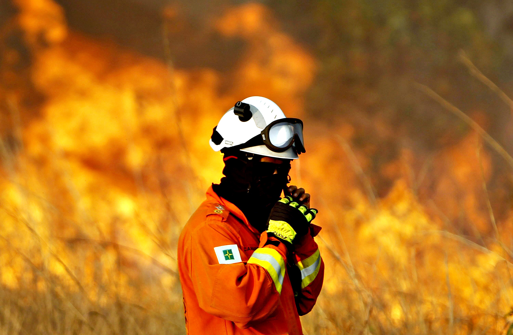 A firefighter adjusts his safety helmet as he tries to extinguish a fire at the park Floresta Nacional in Brasilia, Brazil, 01 September 2014. Six teams, a helicopter and an aircraft were mobilized to contain the fire. The Brazilian capital suffers of current low humidity and a period of drought.