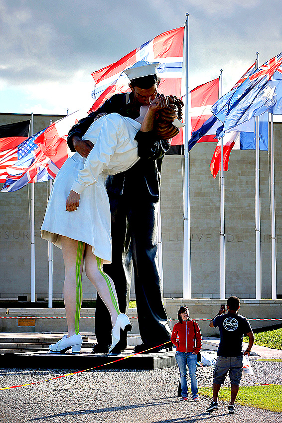 """Unconditional Surrender,"" an 8-meter (25-foot) cast-bronze sculpture in color of a sailor and a nurse in lip-locked embrace, is seen outside the Caen Memorial in Normandy, France, Wednesday, Sept. 24, 2014. The sculpture by Seward Johnson is based on a U.S. Navy photographer s black-and-white snapshot taken on Aug. 15, 1945, according to the Sculpture Foundation, a U.S.-based nonprofit that owns the work. It also resembles a famous photograph taken by Life magazine Alfred Eisenstaedt on that day. The sculpture is to spend a year outside the Caen Memorial, a museum focusing on World War II."
