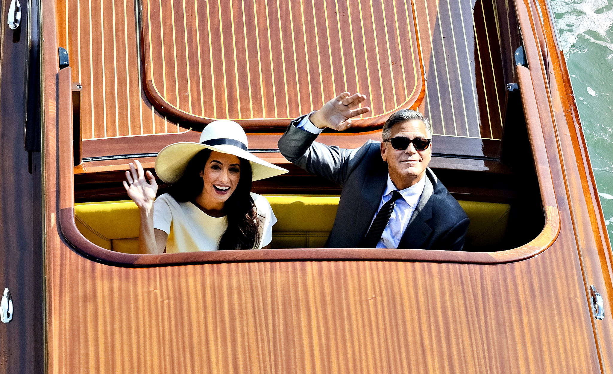 Actor George Clooney and Amal Alamuddin wave from a boat as they leave after a civil wedding ceremony at the town hall in Venice, Italy, Monday, Sept. 29, 2014. George Clooney married human rights lawyer Amal Alamuddin Saturday, the actor's representative said, out of sight of pursuing paparazzi and adoring crowds.