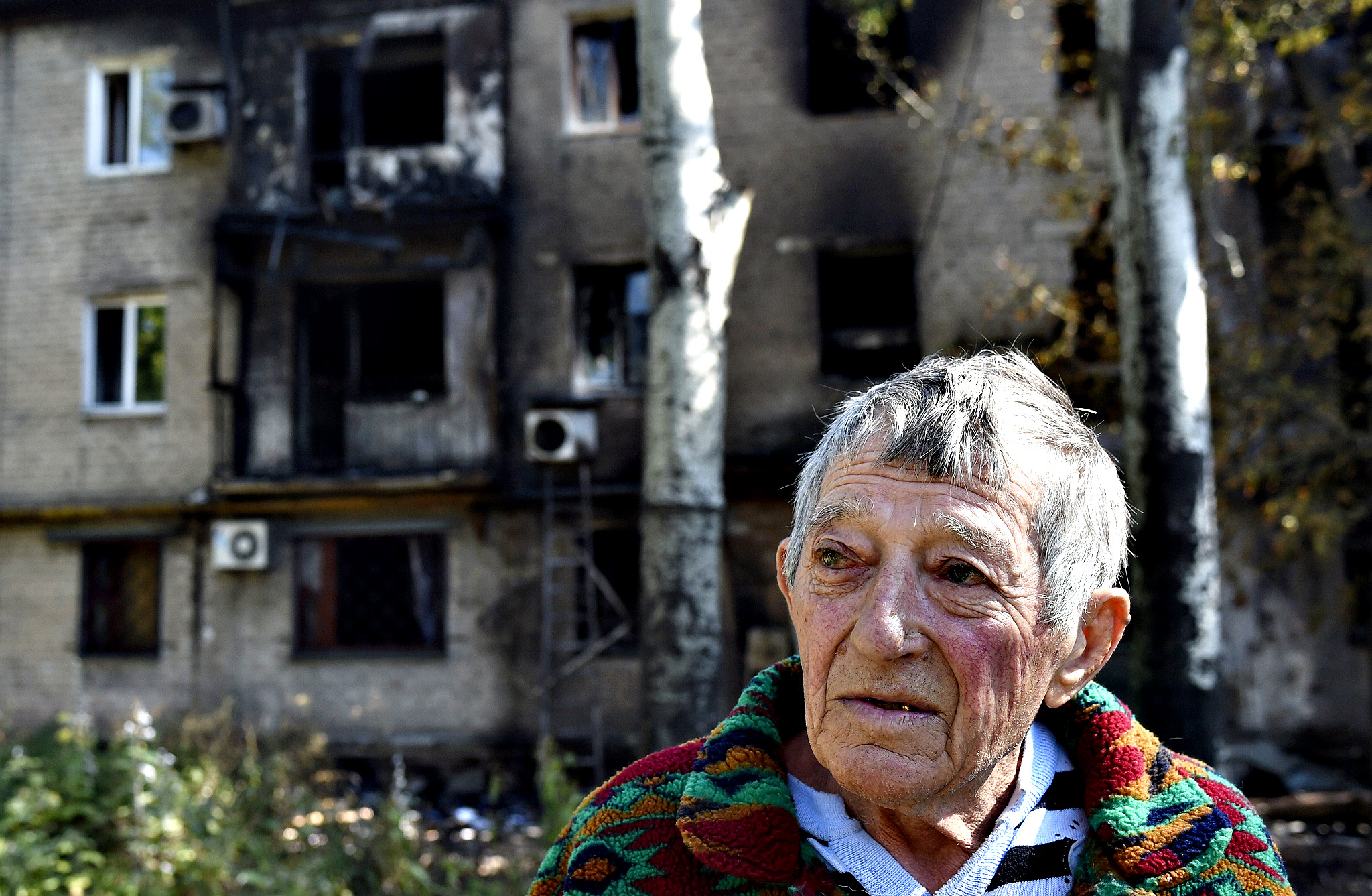 A man who left his burned flat stands in front of a building destroyed by shelling this morning in the Kievsky district near the international airport on September 17, 2014 in Donetsk, eastern Ukraine.  Two civilians were killed in fighting in the rebel-held eastern Ukrainian city of Donetsk, where fierce battles were raging near the airport on Wednesday, city hall said.