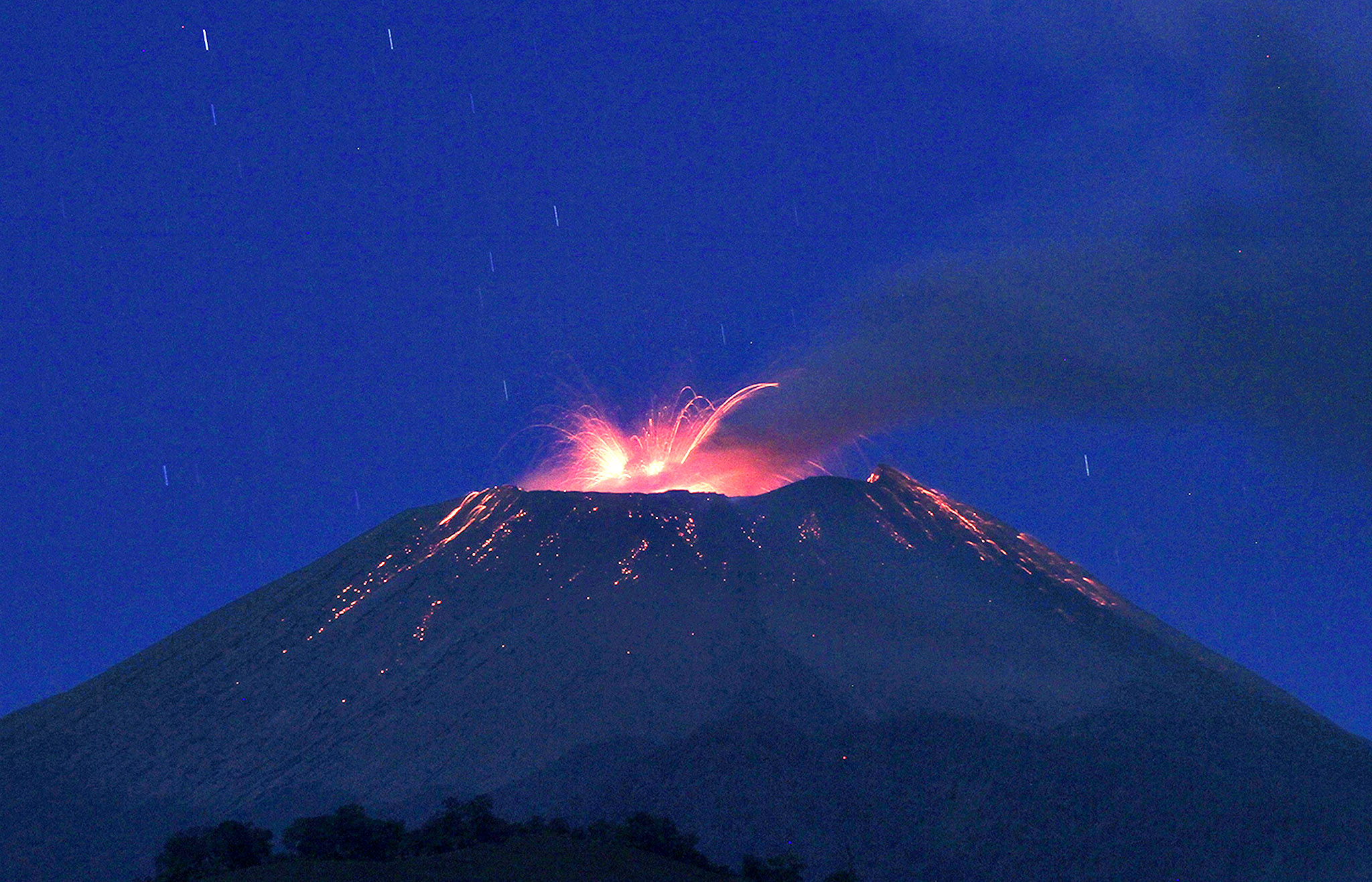 A long exposure photo shows smoke rising as lava flows from the crater of Mount Slamet volcano before dawn, as seen from Brebes town in Indonesia's Central Java province on September 12, 2014. Indonesian authorities have put the Mount Slamet volcano on the second-highest alert level after it erupted 38 times on September 11, spewing lava some 1500 metres (5,000 feet) into the air. Authorities warned residents to remain outside a four-kilometre radius of the volcano.