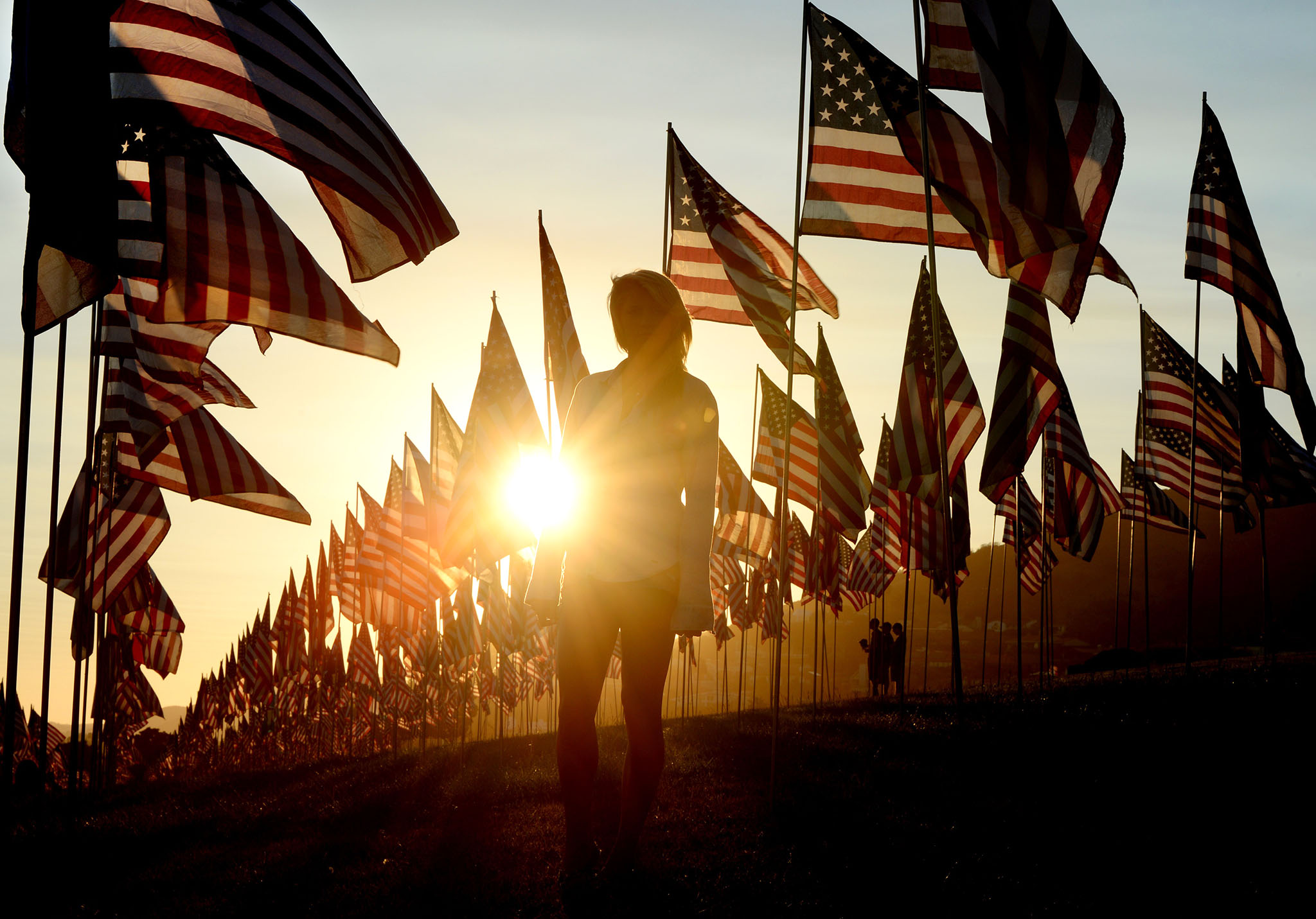 A woman (C) walks amongst US national flags erected by students and staff from Pepperdine University to honor the victims of the September 11, 2001 attacks in Malibu, California on September 9, 2014. The students placed some 3,000 flags in the ground in tribute to the nearly 3,000 victims lost in the attacks almost 13 years ago. AFP PHOTO / Mark RALSTONMARK RALSTON/AFP/Getty Images
